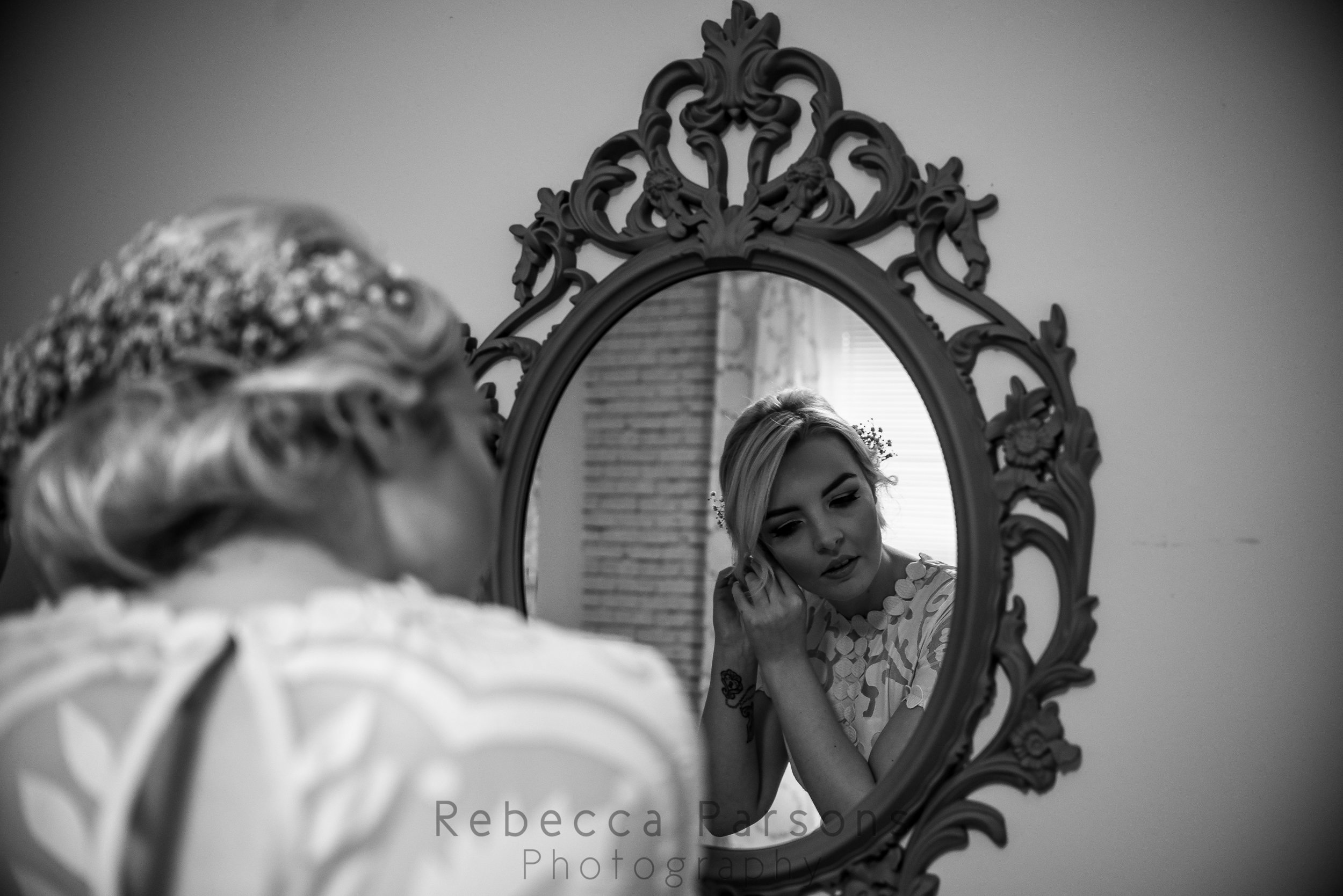 Bride putting earrings on in front of mirror black and white