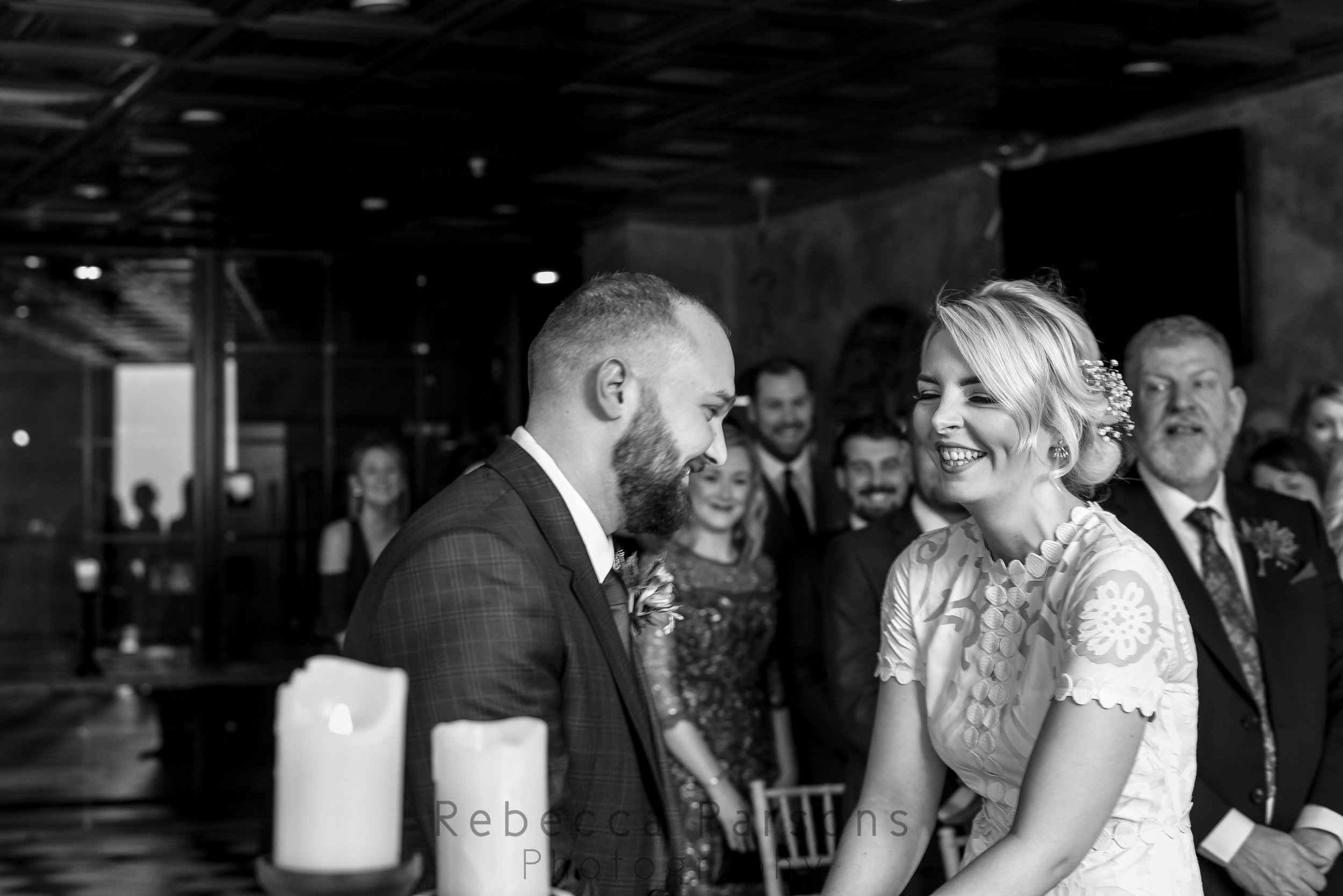 Bride and groom laughing at altar black and white
