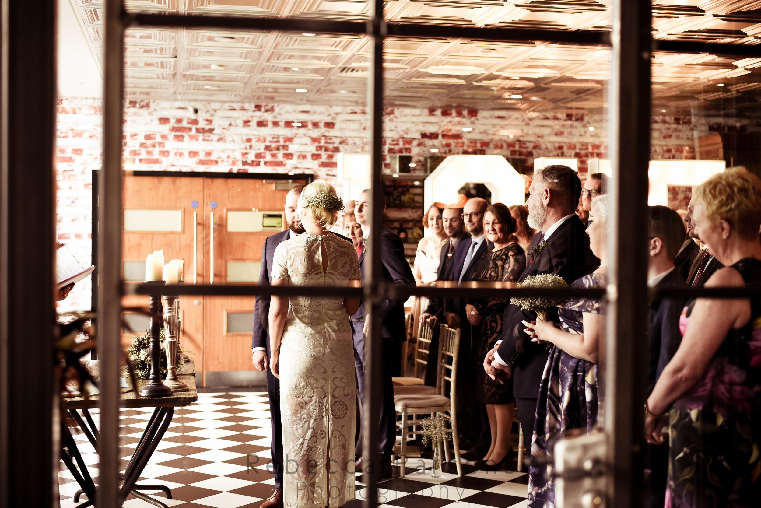 Bride and groom saying vows through doorway