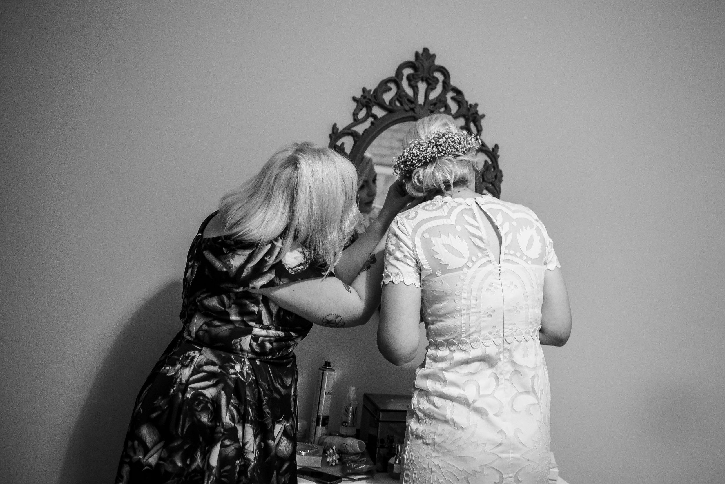 Bride's sister helping her with earrings