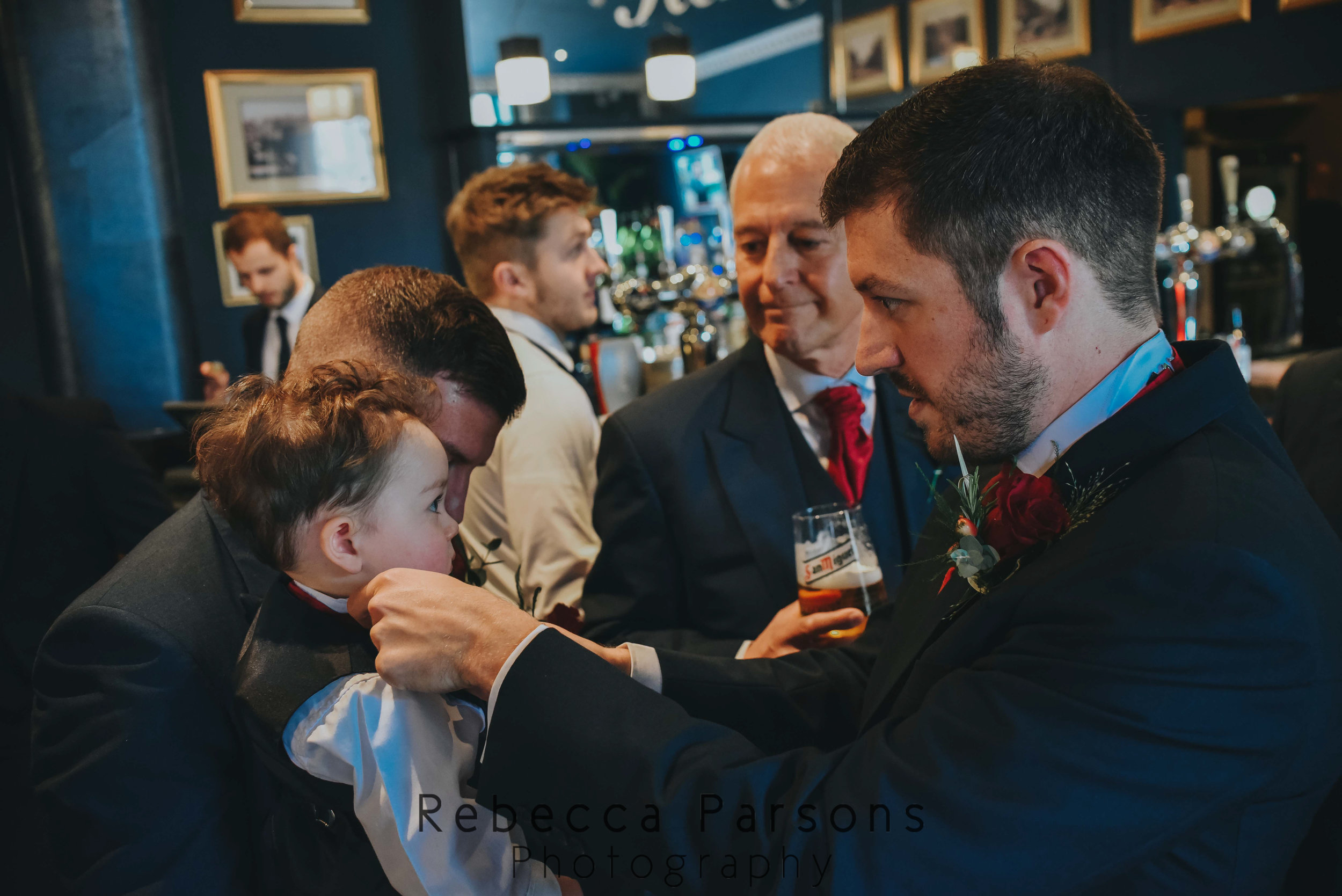 groom adjusting son's bow tie while father looks on