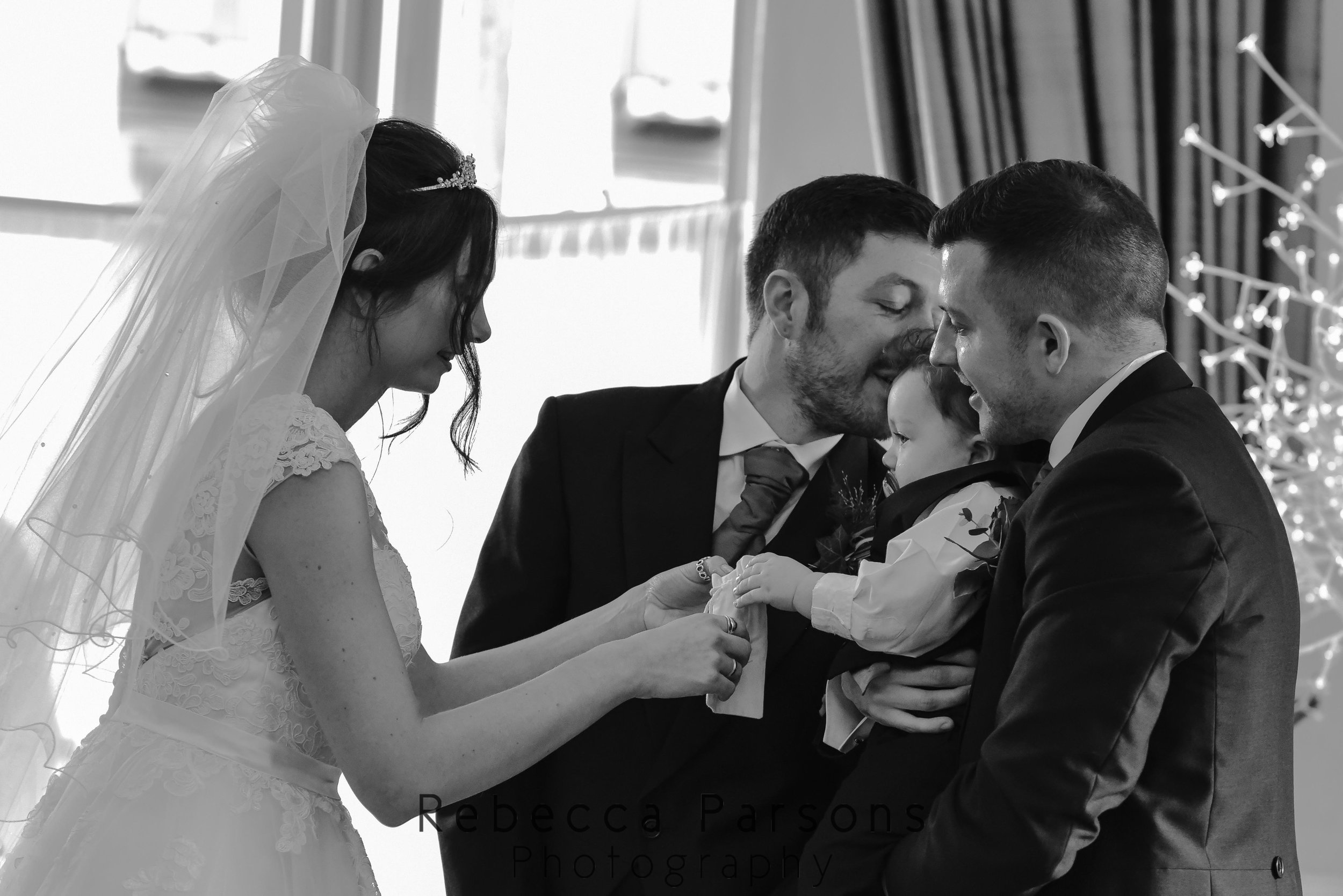 bride and groom exchanging rings and son being held by uncle