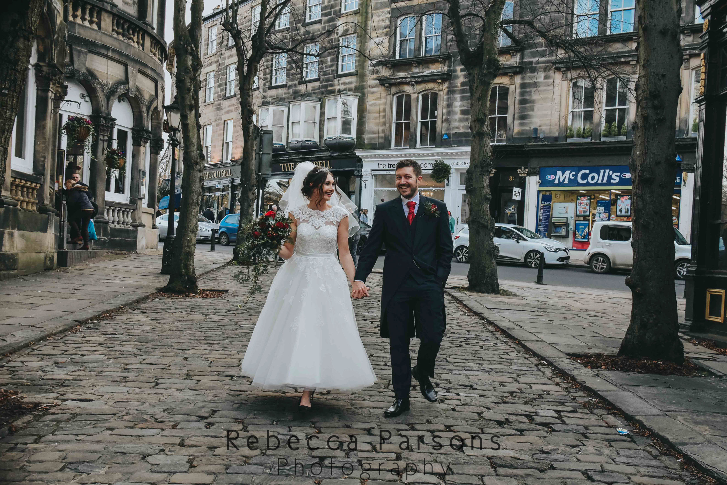 bride and groom walking down cobbled street