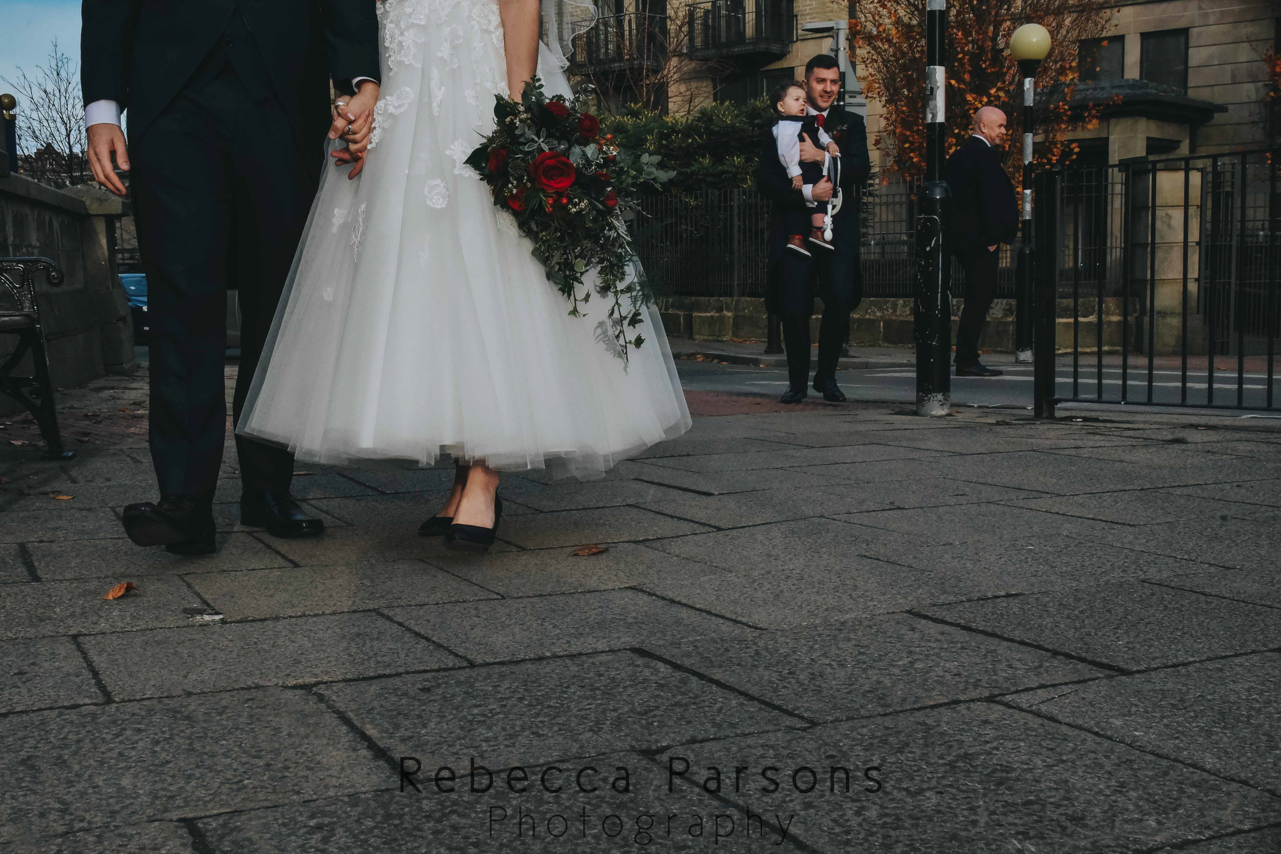 bride and groom shoes with son in background