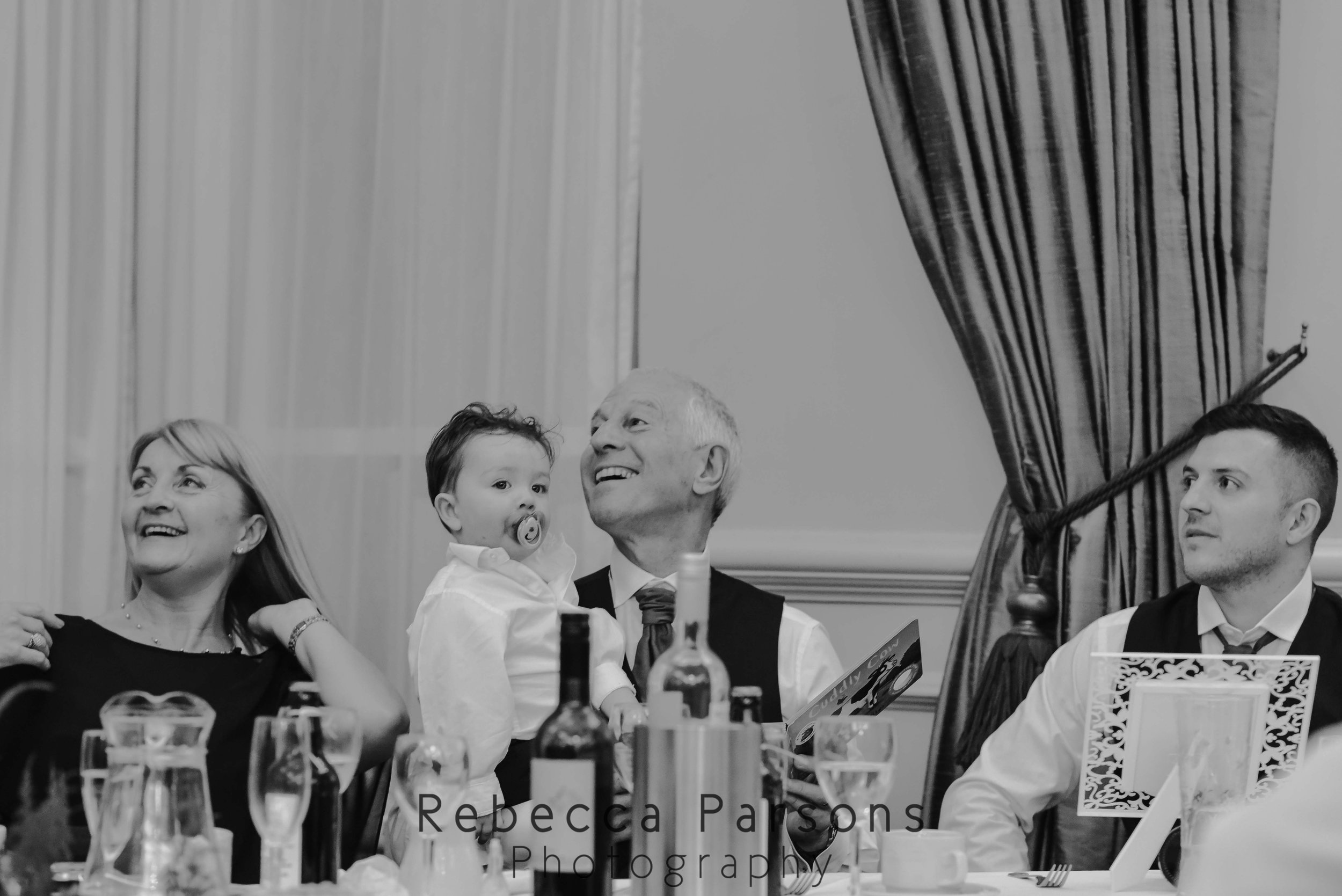 family of groom listening to speeches black and white