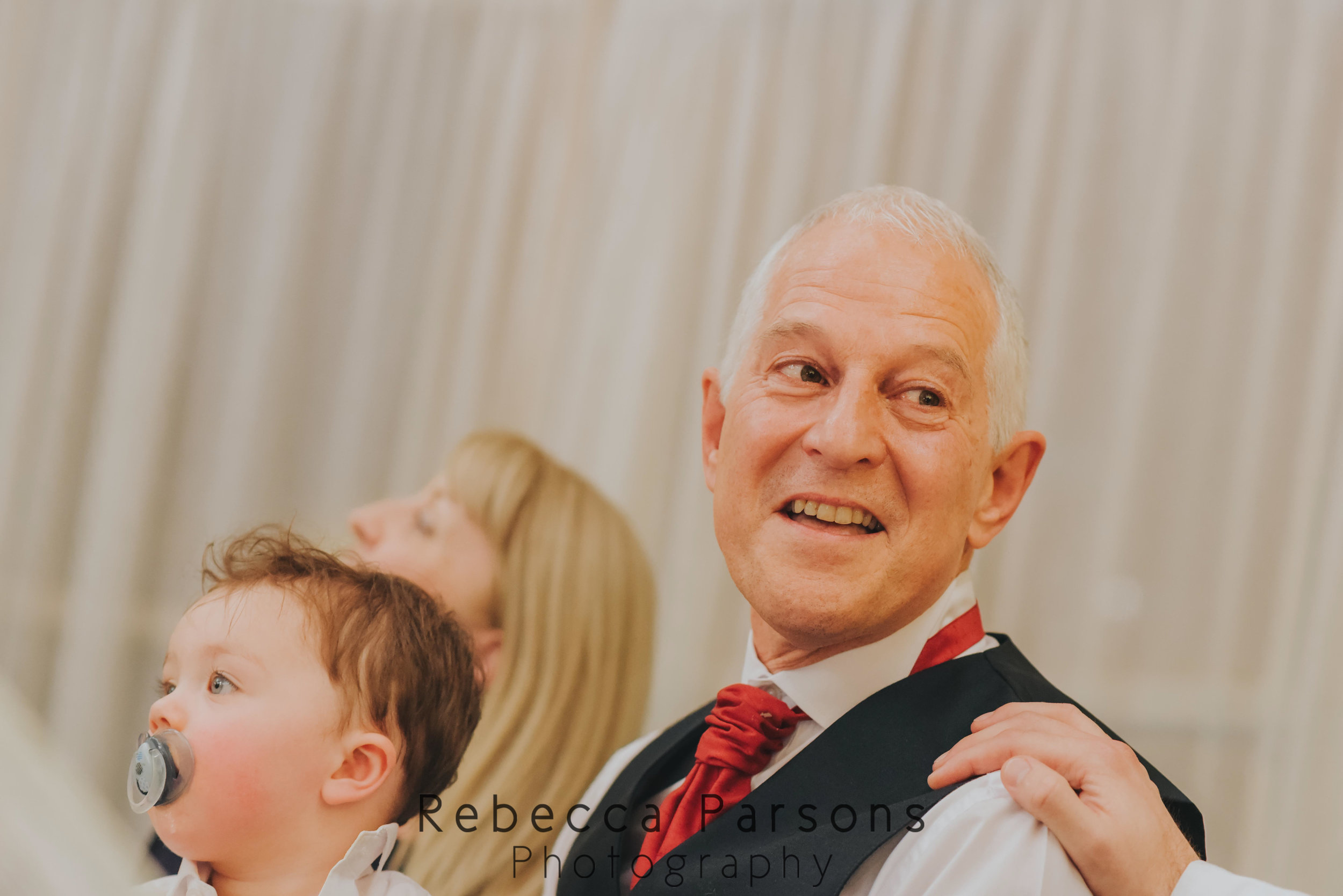 father of groom laughing with hand on shoulder