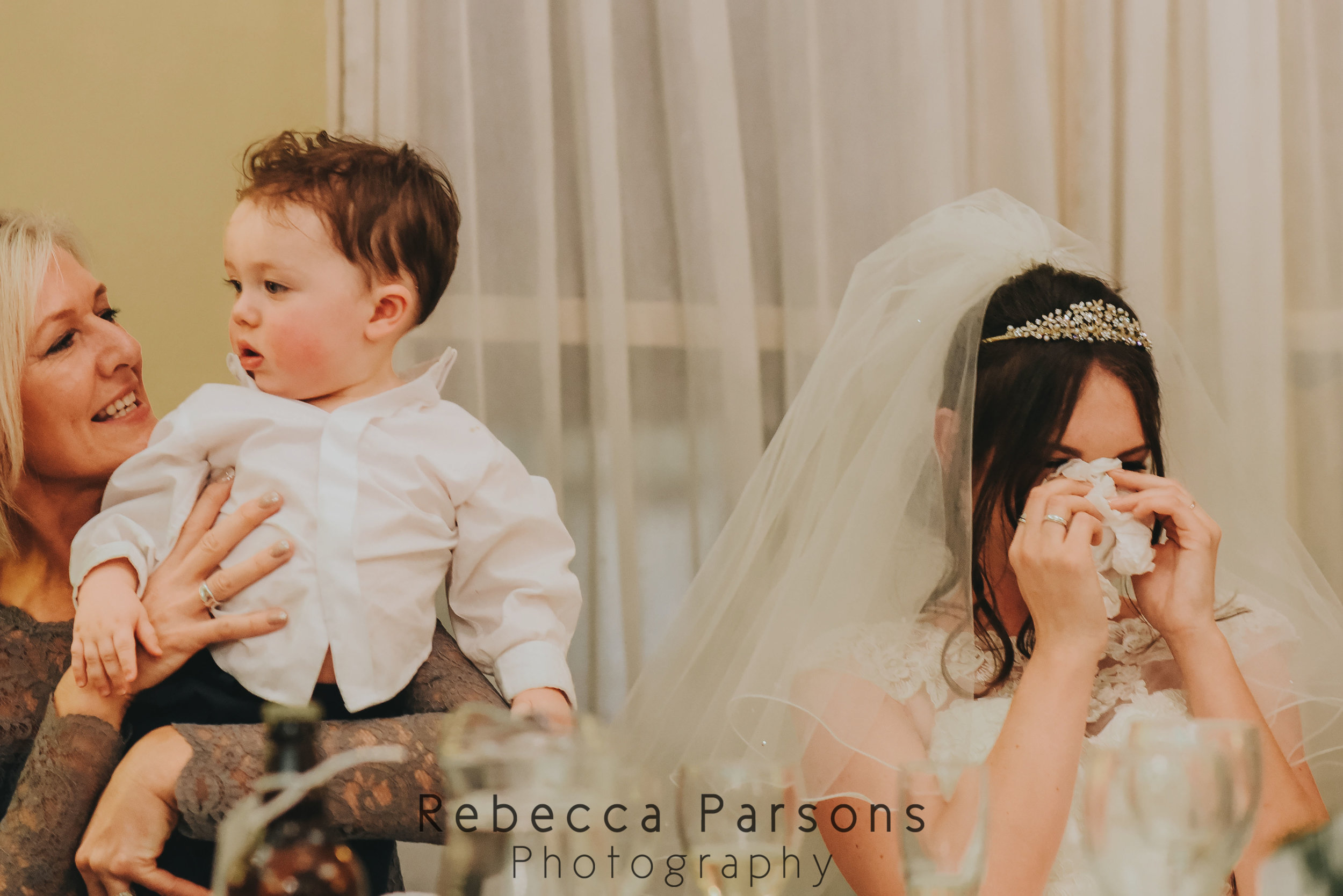 bride wiping eyes while mother holds son