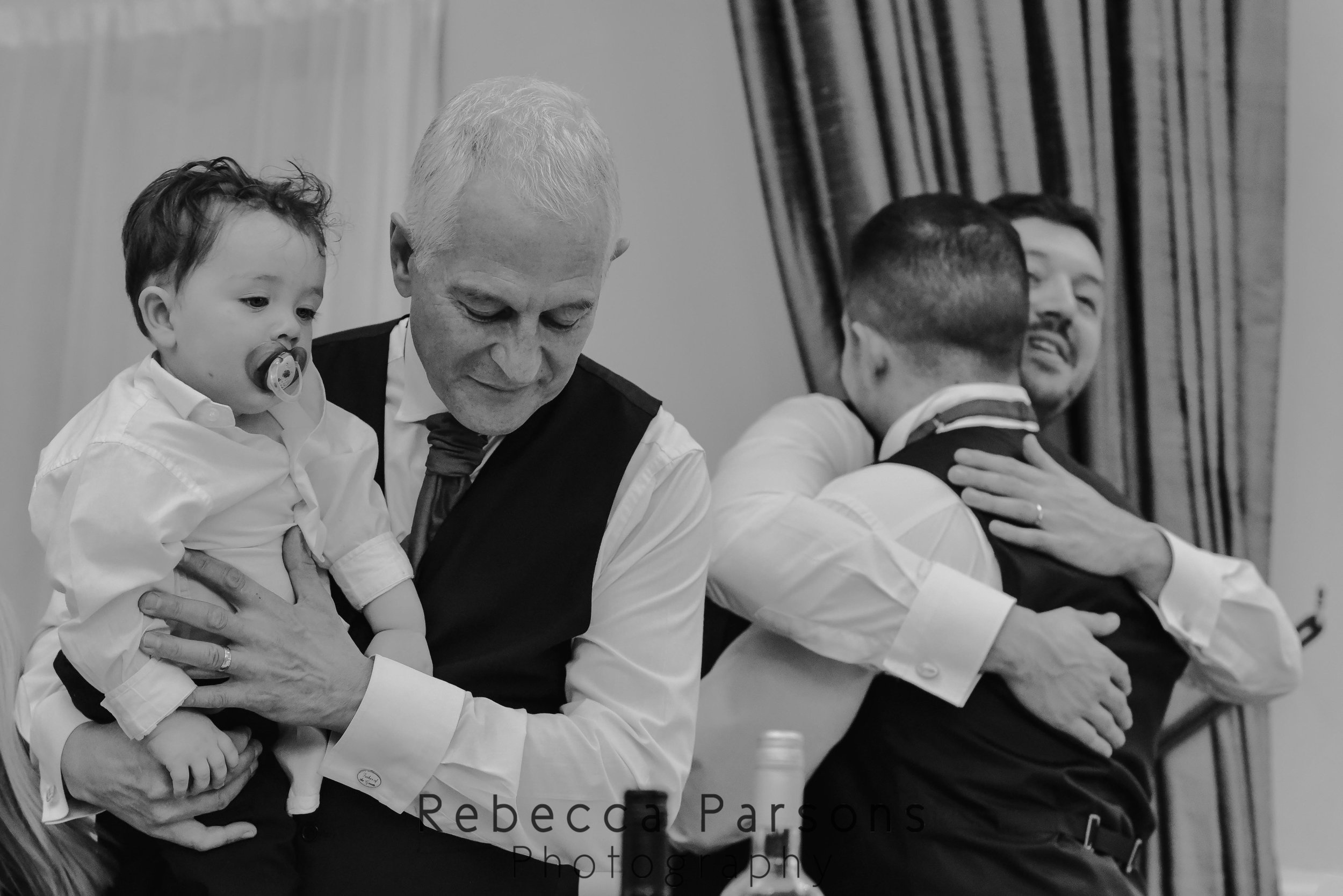 groom hugging brother while father holds son