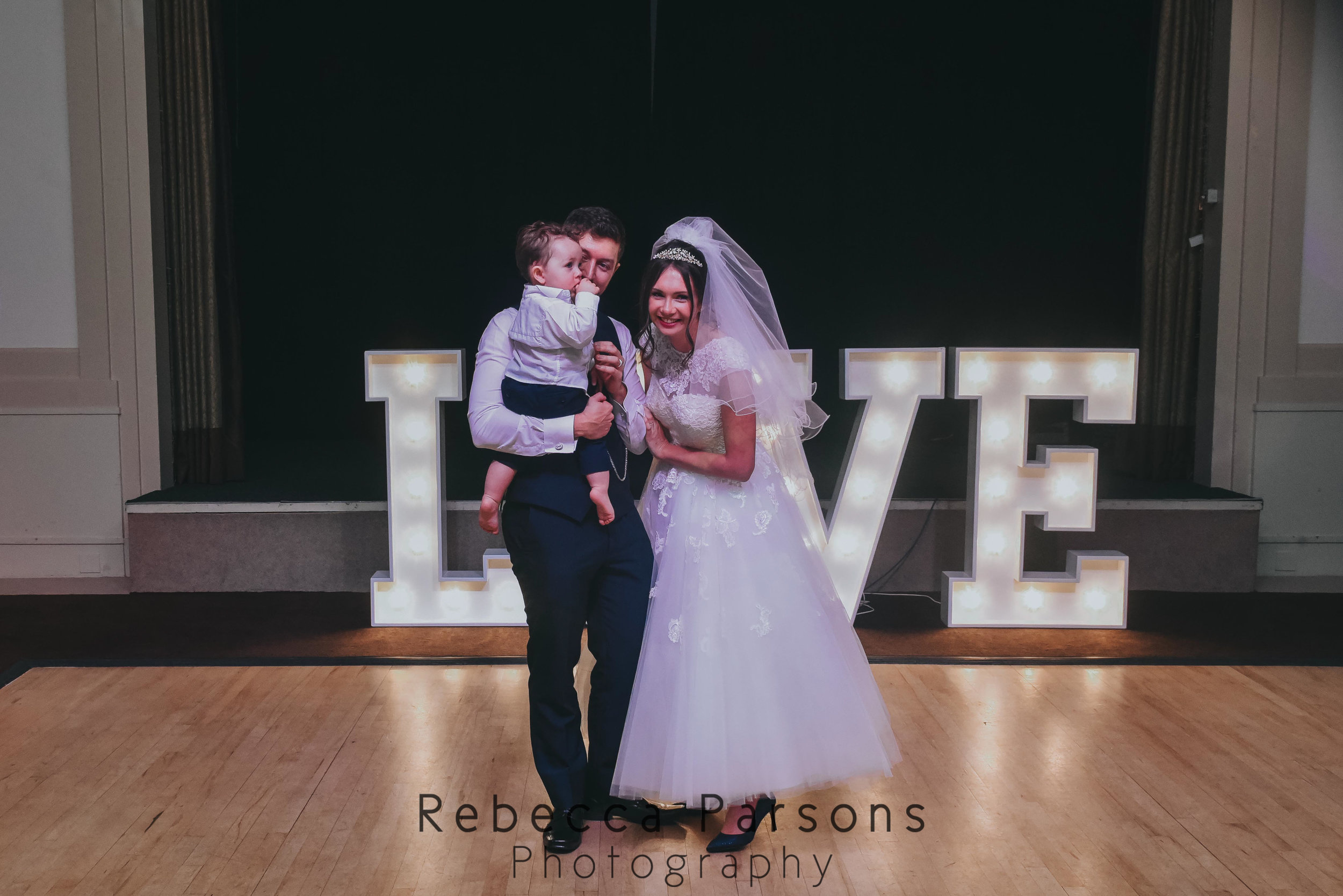 bride and groom on dancefloor with son in front of love letters