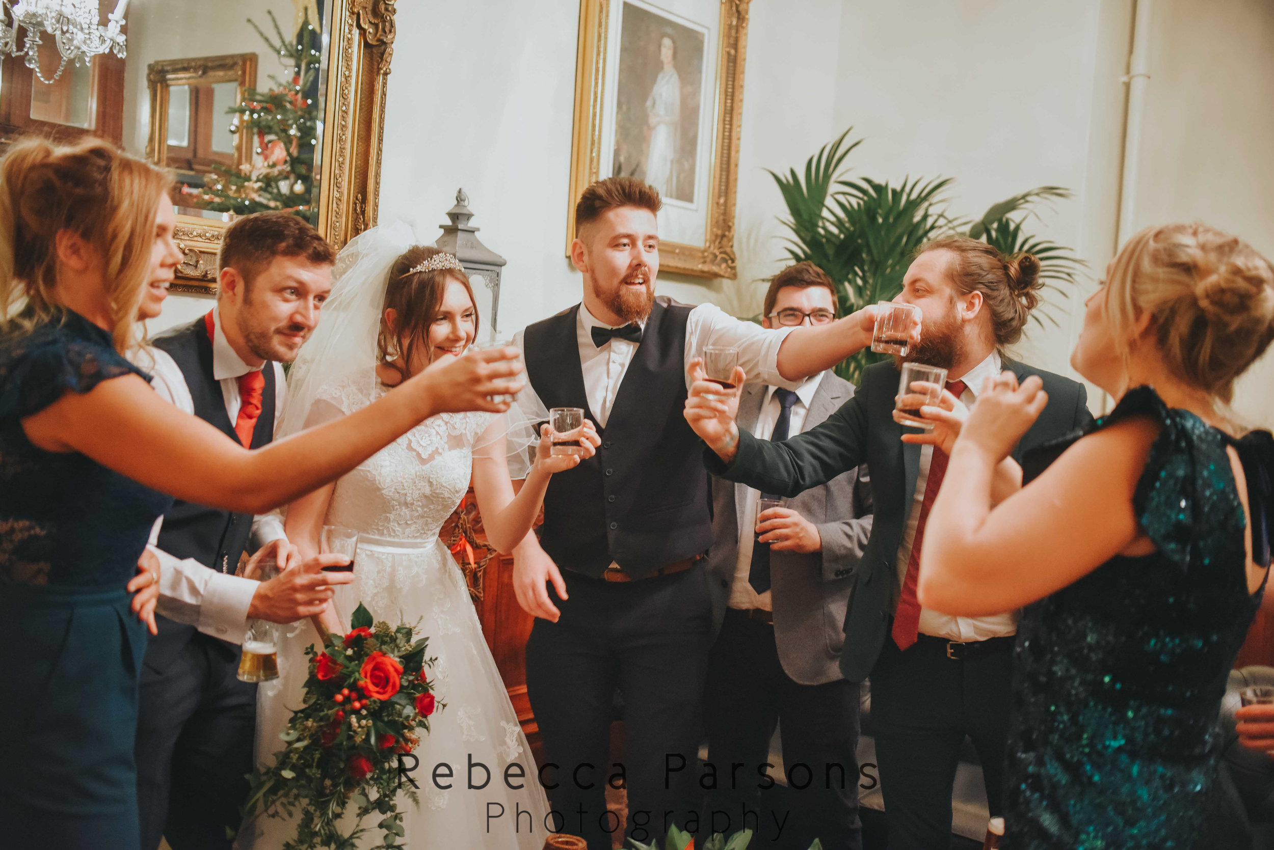 bride and groom doing shots with group of friends