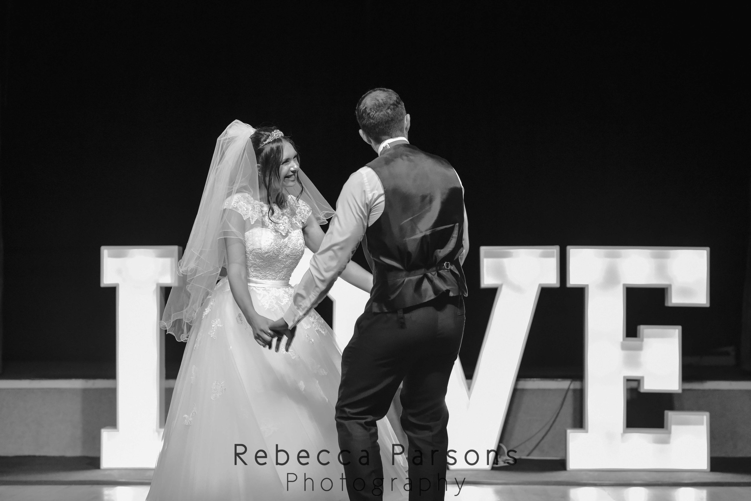 bride and groom dancing in front of love letters black and white