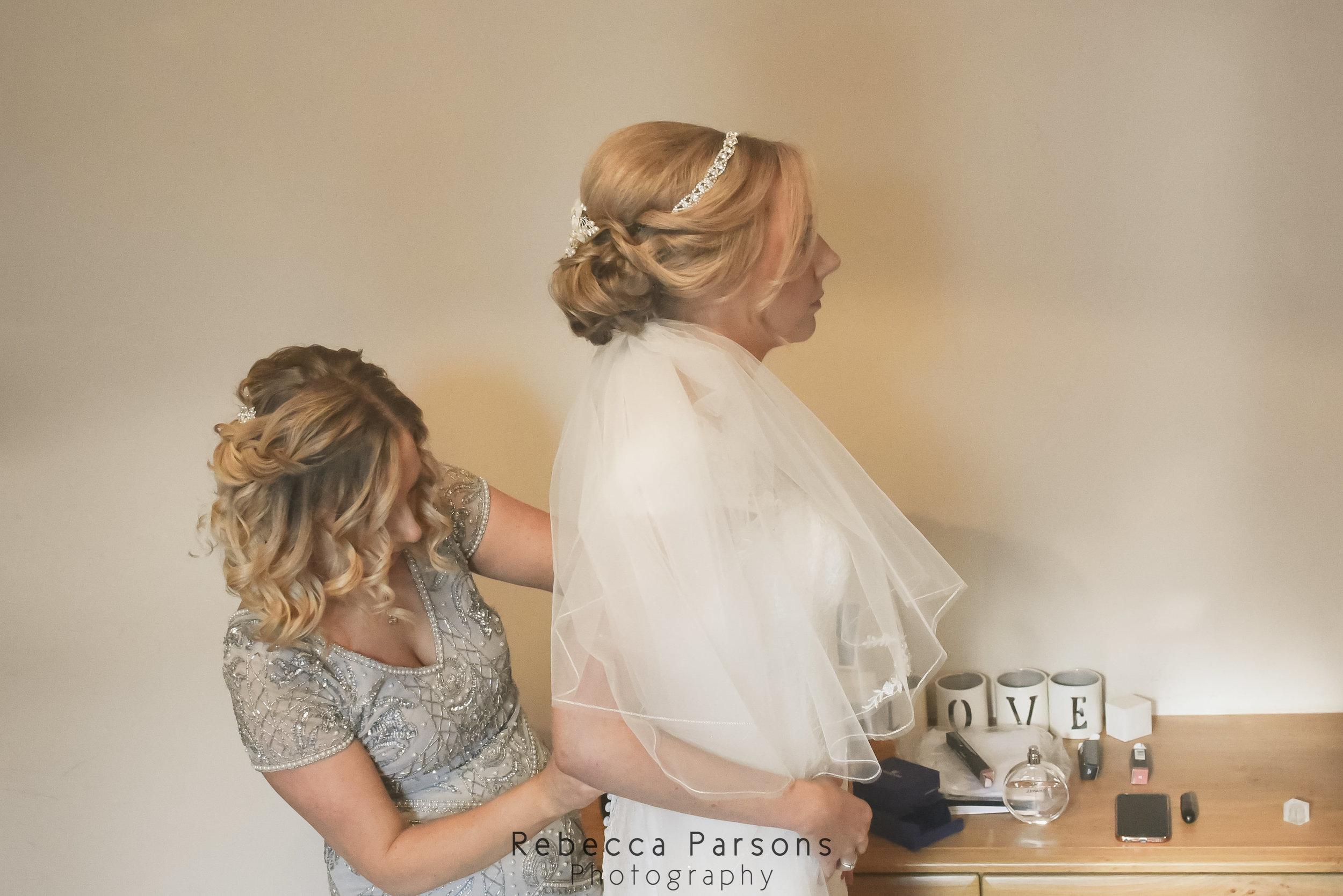 maid of honour fastening brides dress