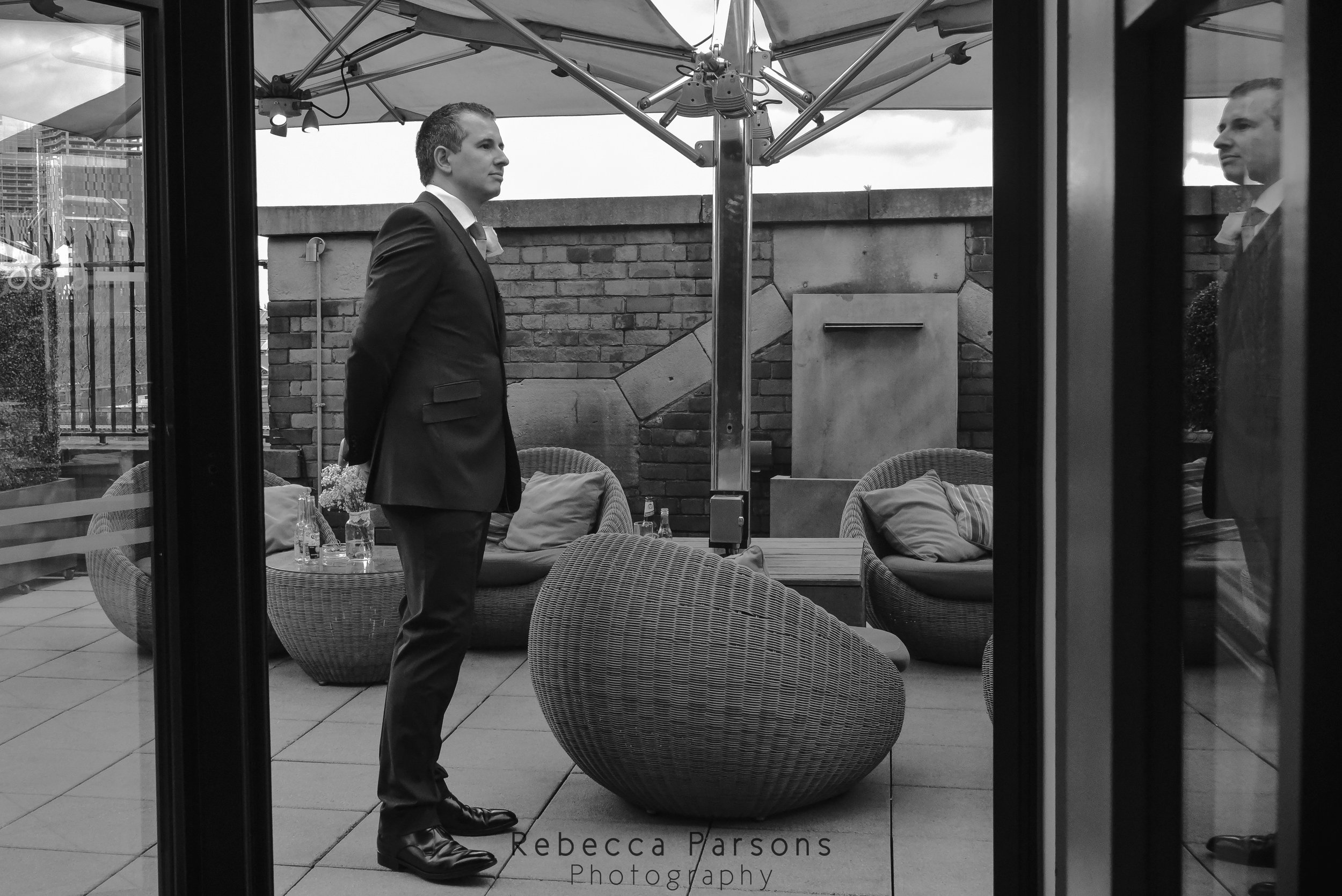 groom waiting outside black and white