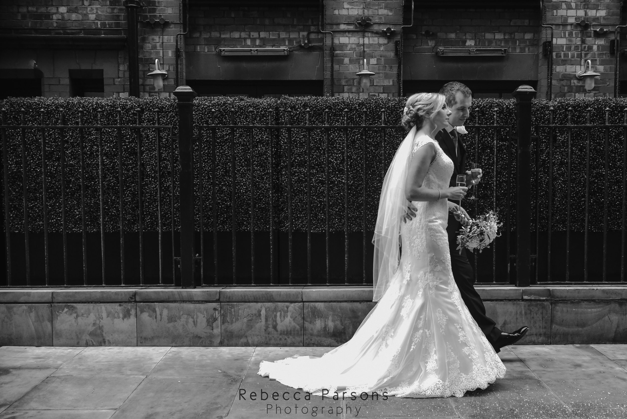 black and white bride and groom walking through spinningfields