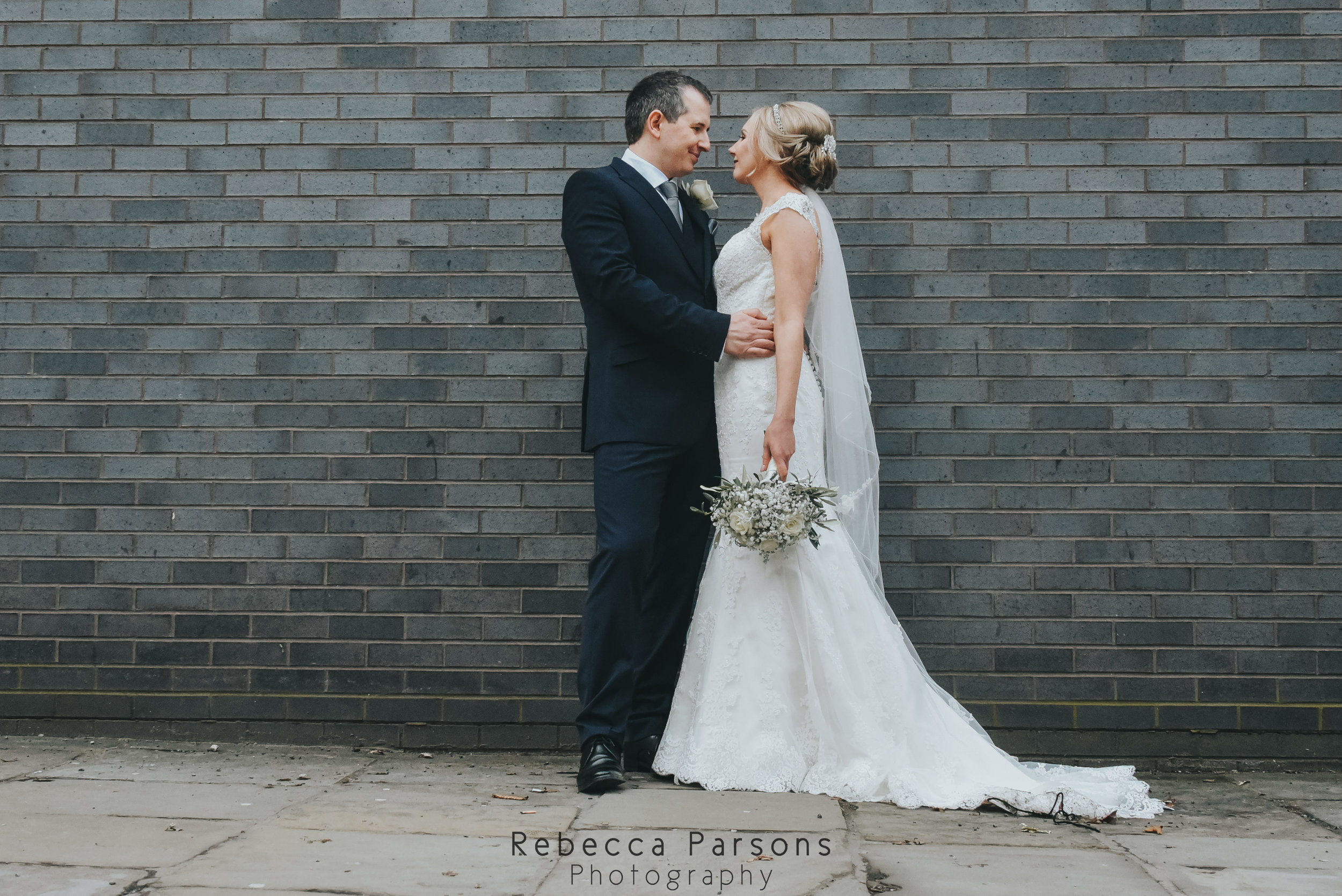 bride and groom looking at each other in front of a wall