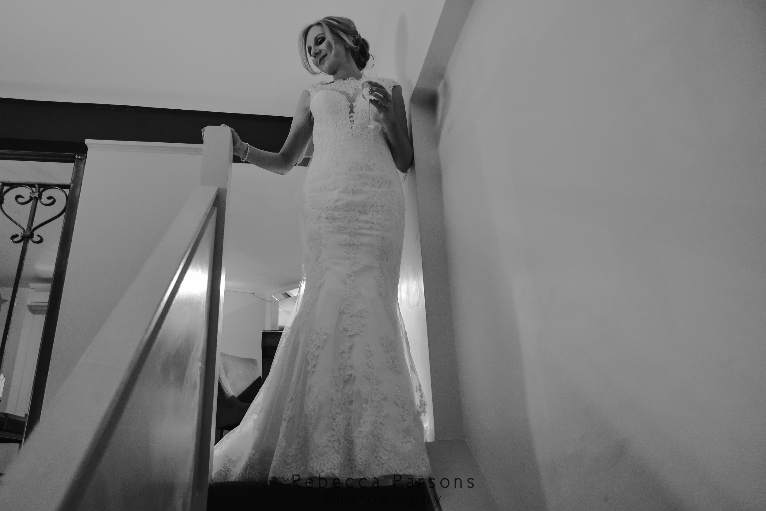 black and white bride at top of stairs