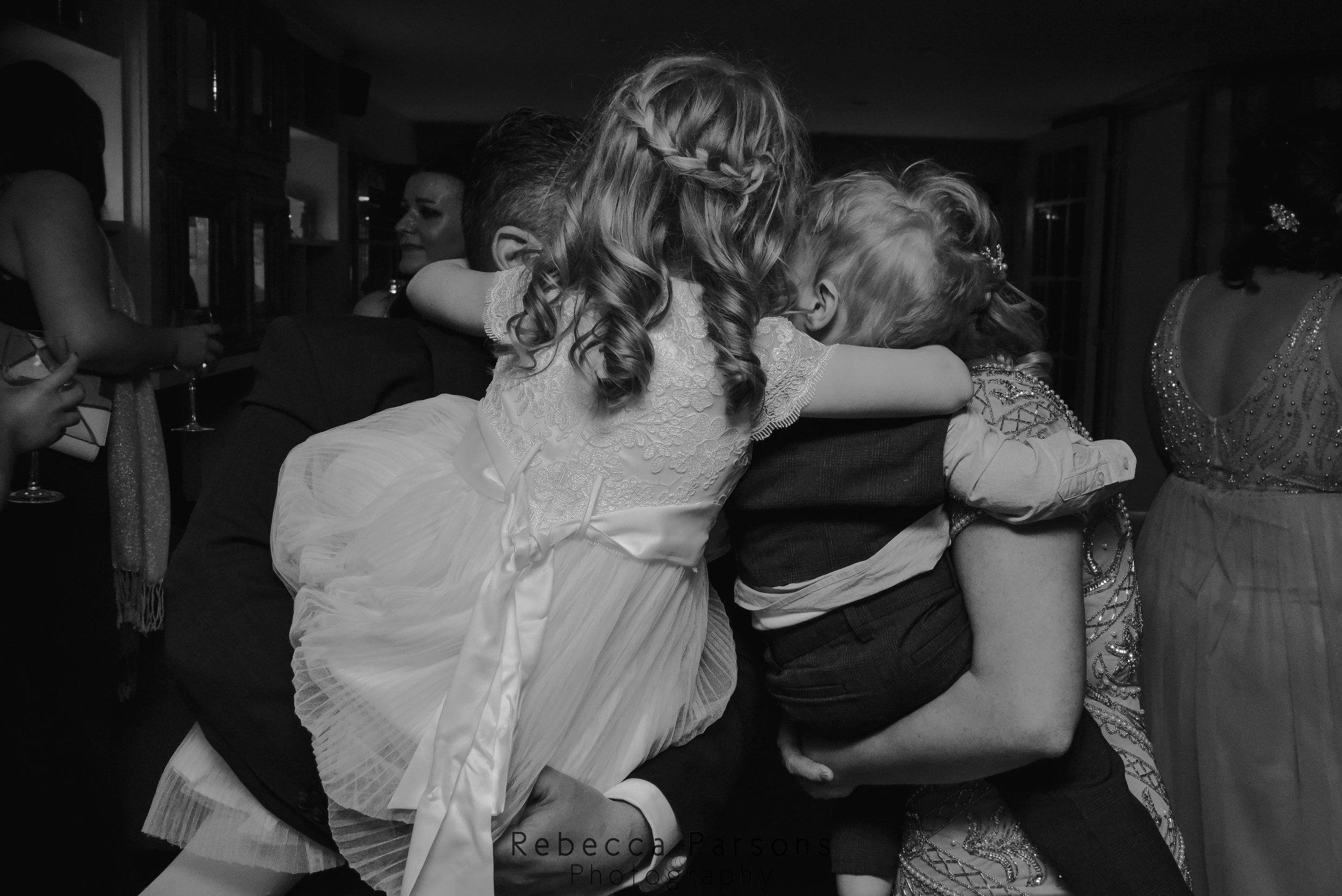 family hugging on dance floor black and white