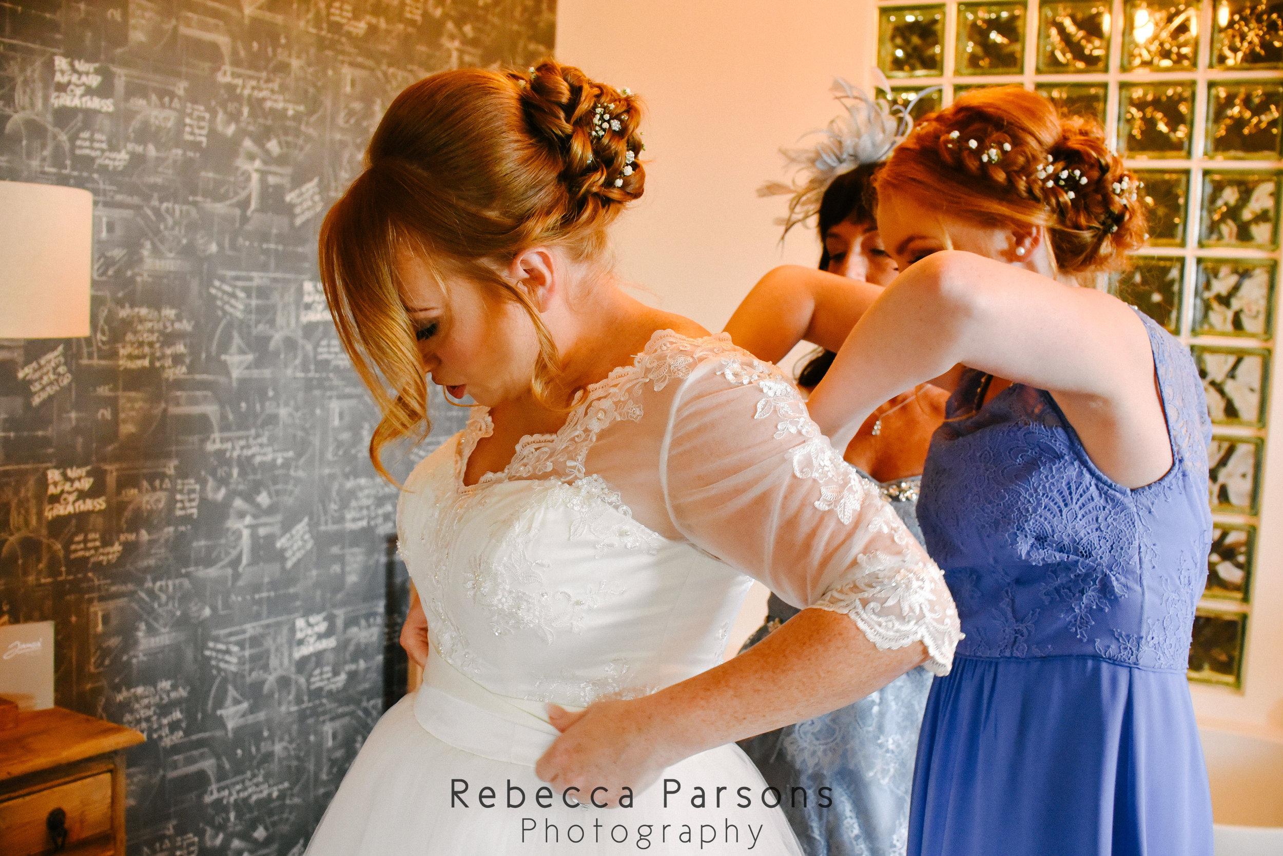 daughter of bride buttoning wedding dress