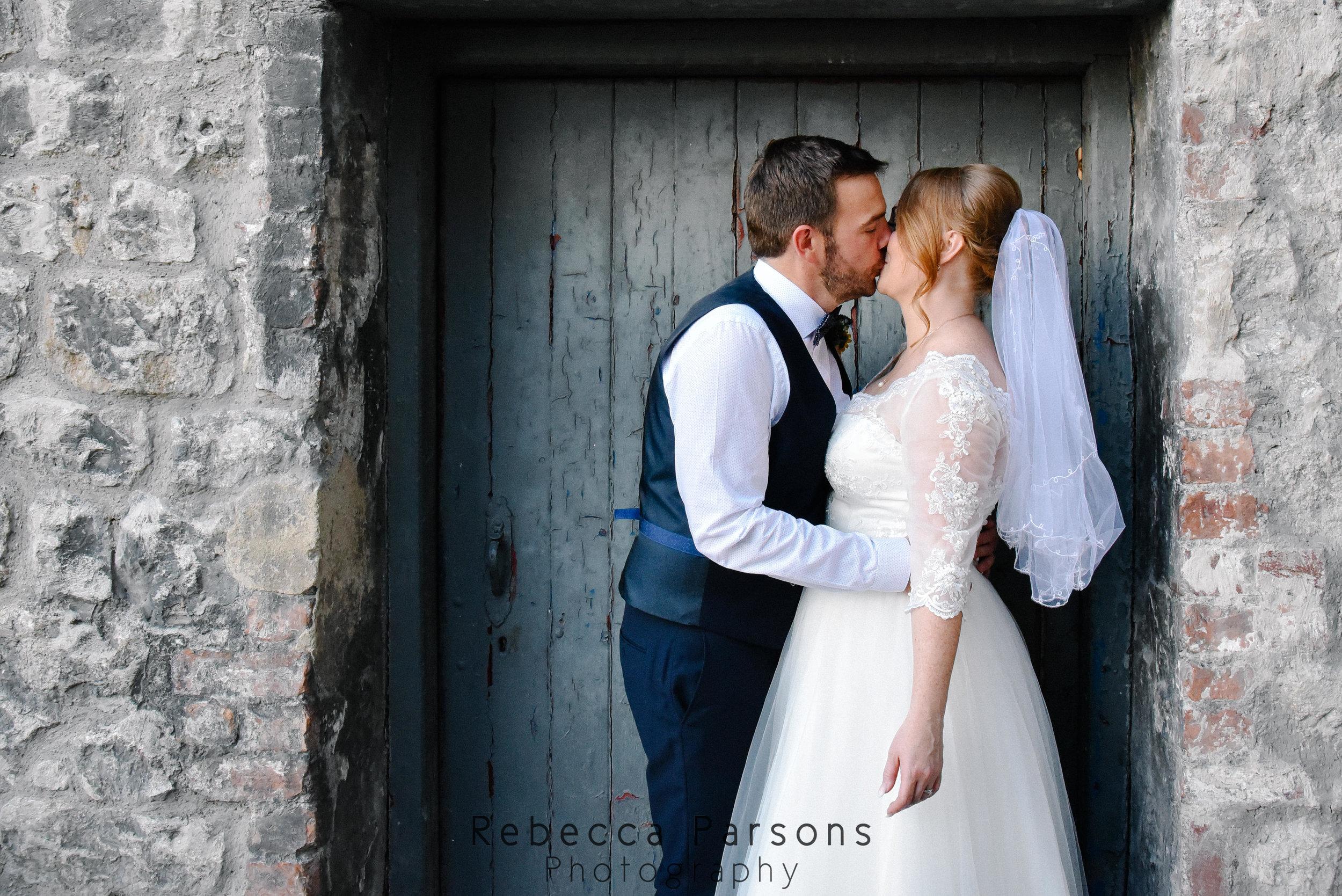 bride and groom kissing in doorway