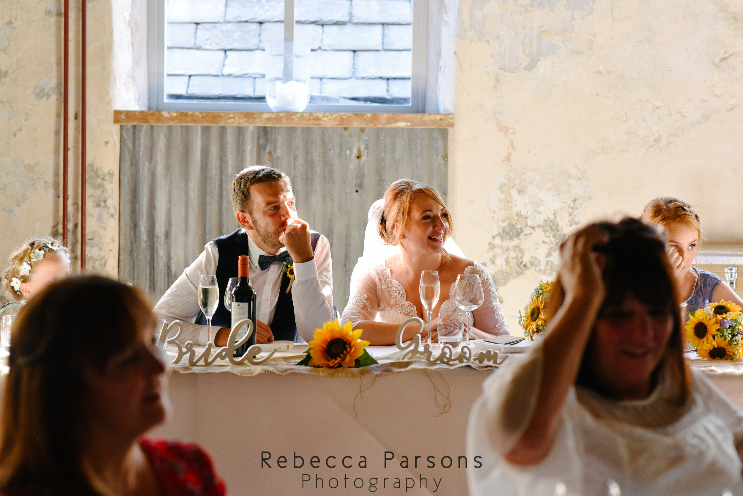 bride and groom sitting down at speeches