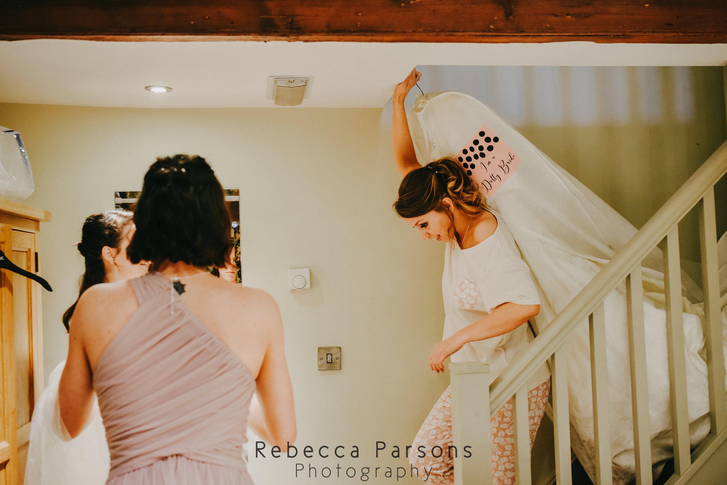 bridesmaids helping bride into dress