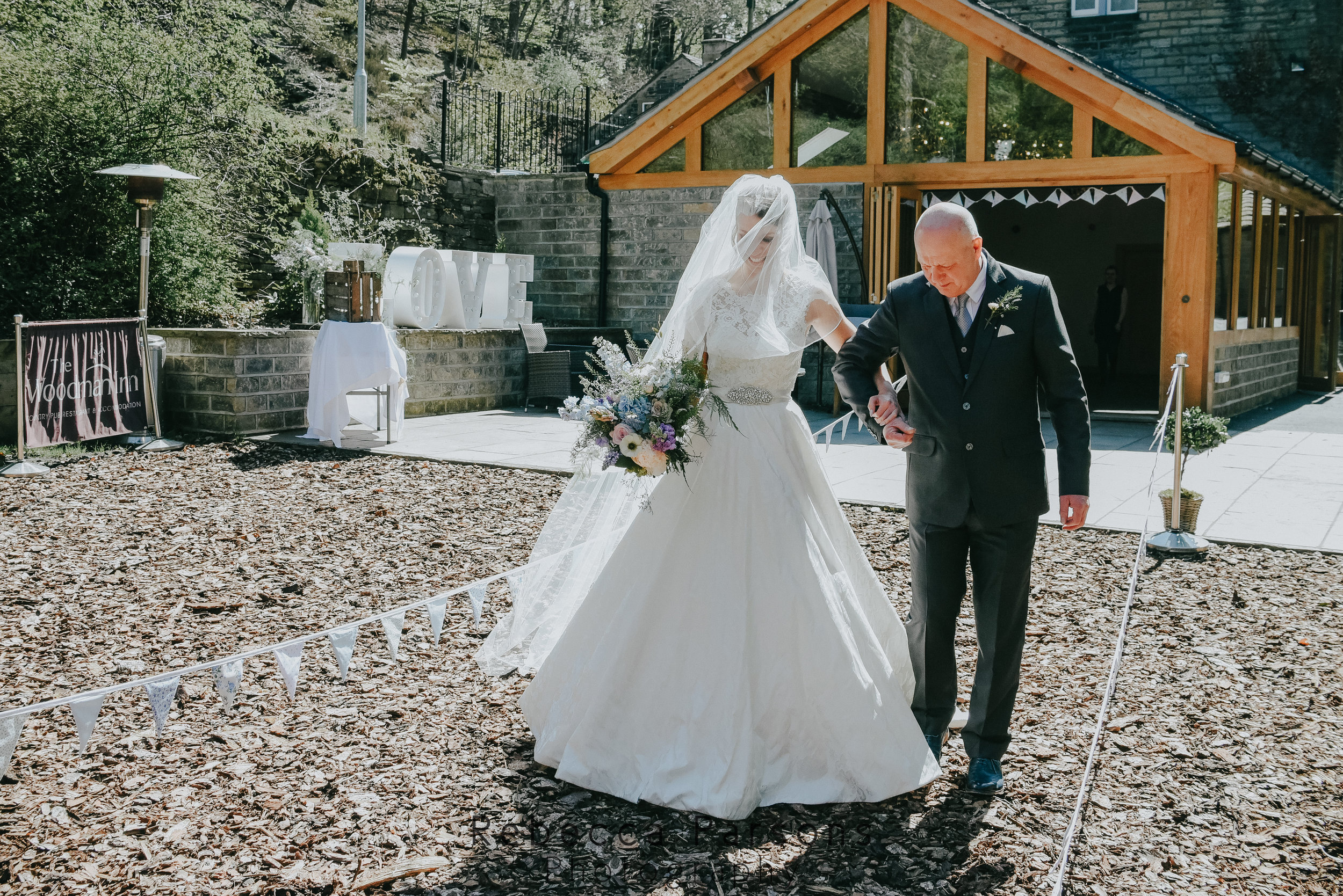 bride and father walking down outside aisle