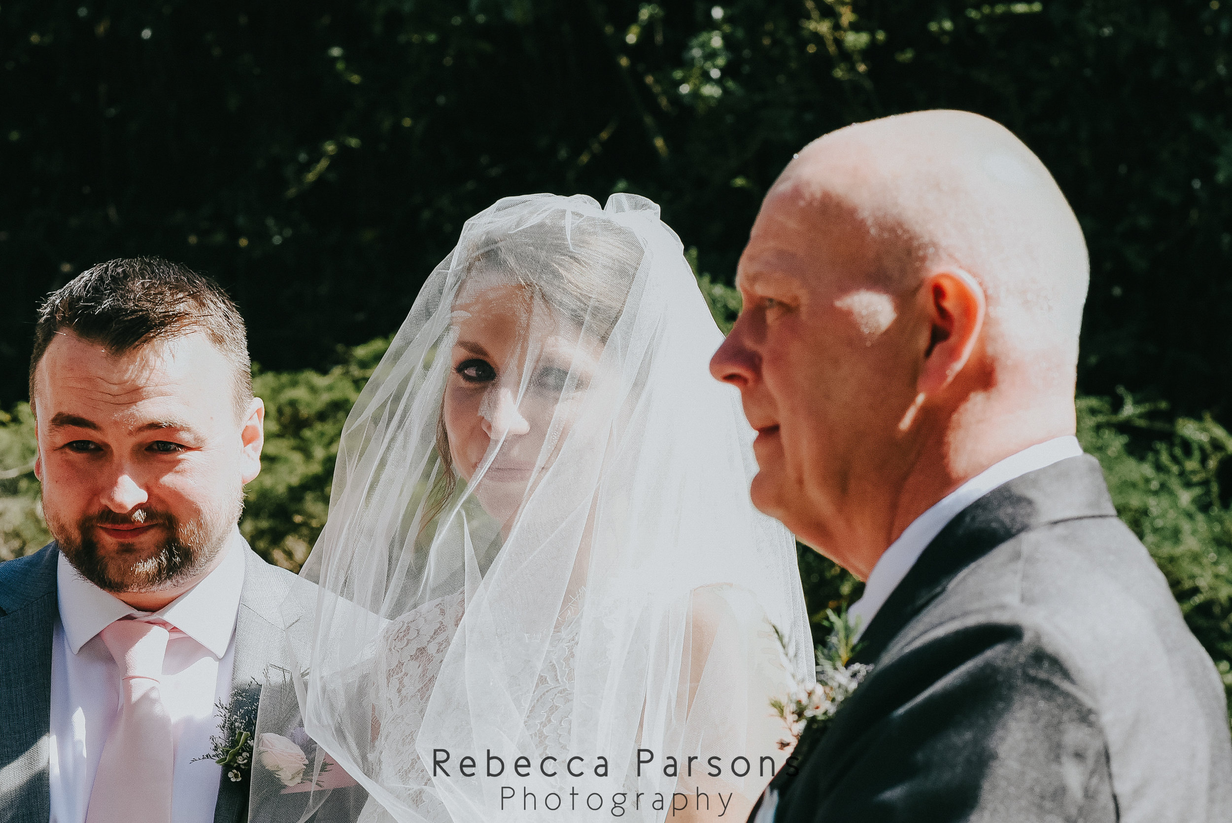 bride and groom and father smiling