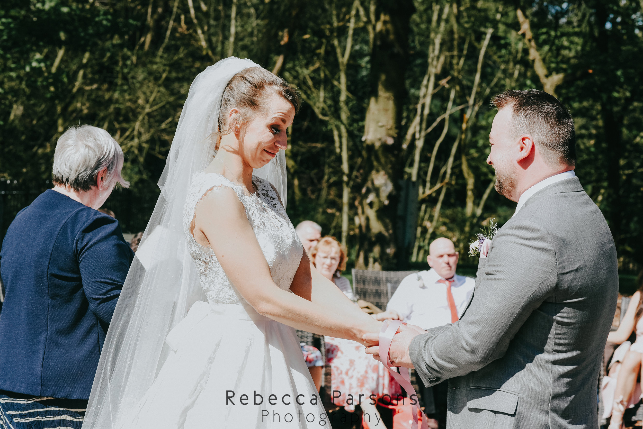 bride and groom holding hands during hand fasting
