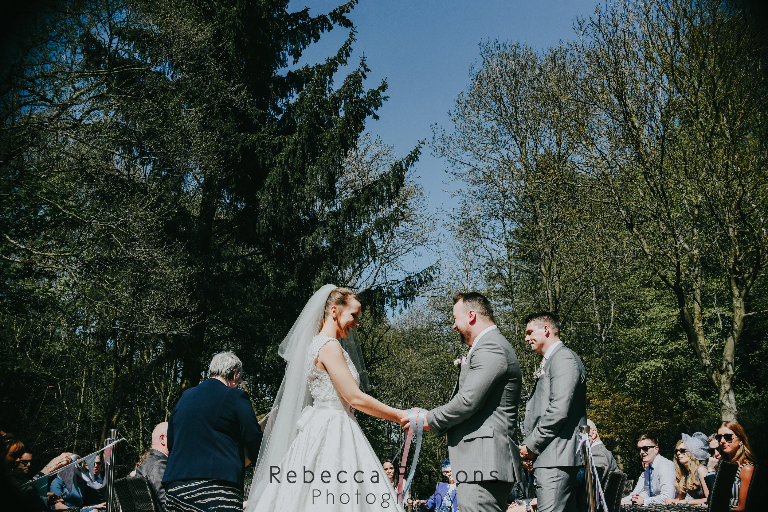 bride and groom holding hands in front of woodland