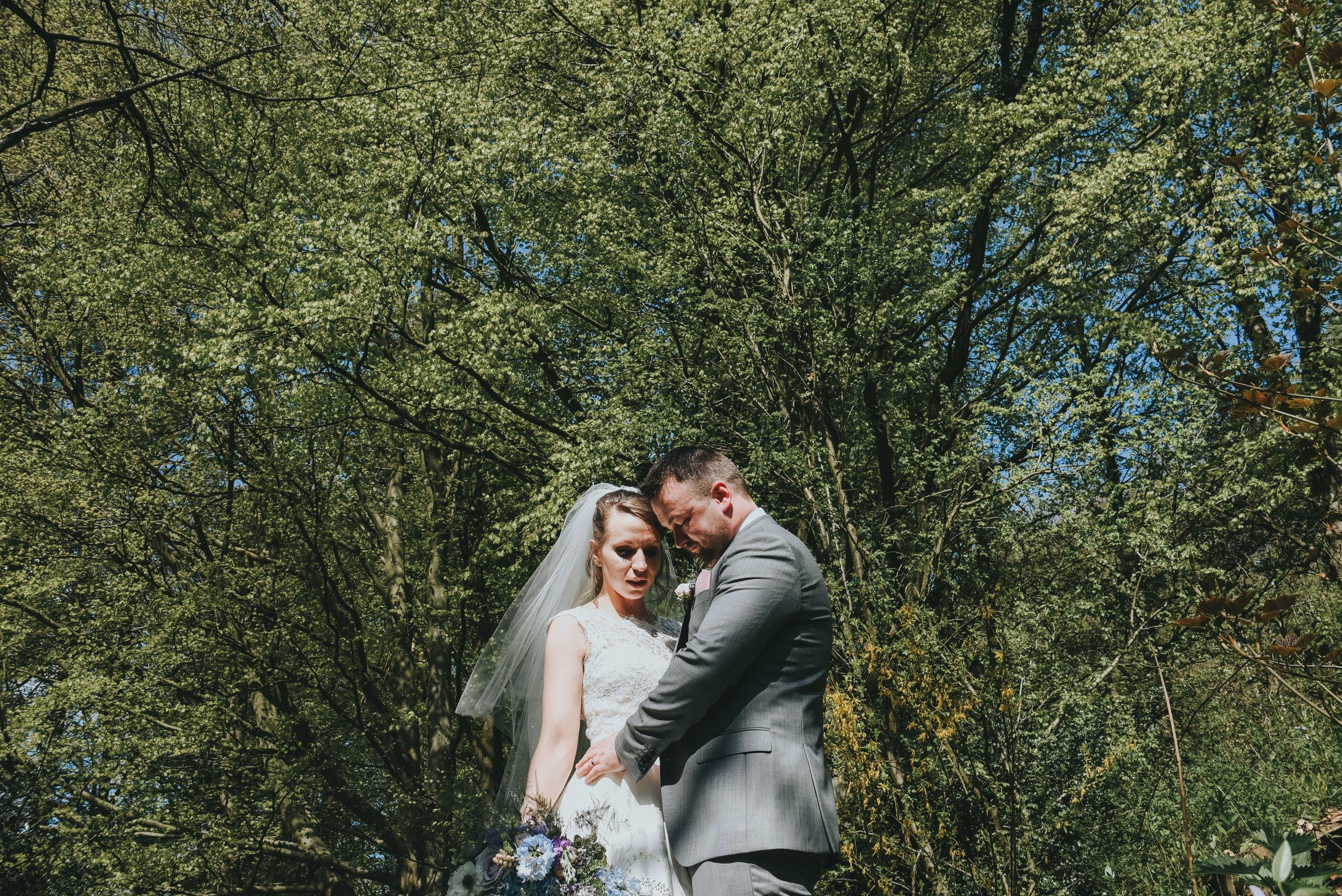 bride and groom cuddling in woodland