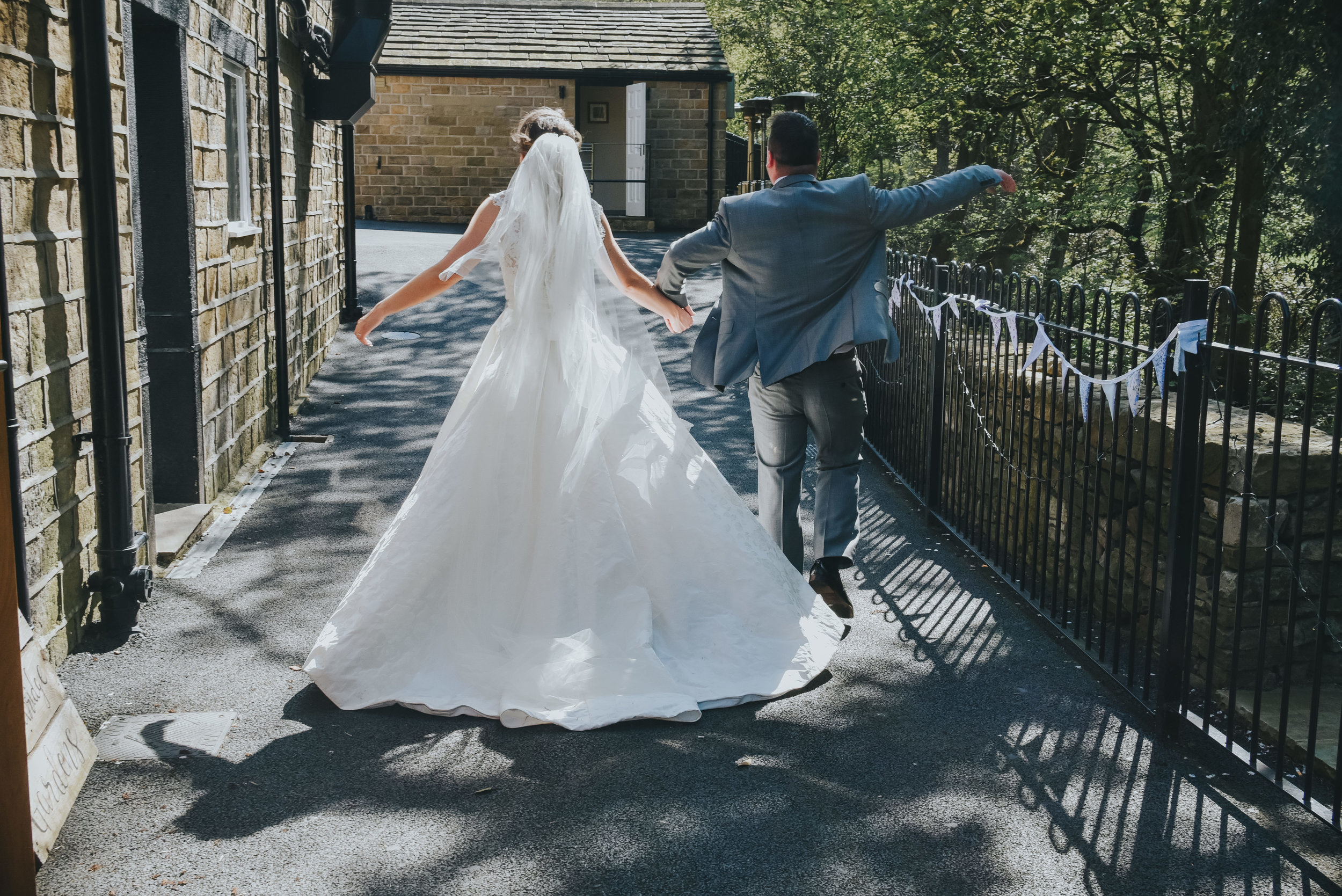 bride and groom arms in air
