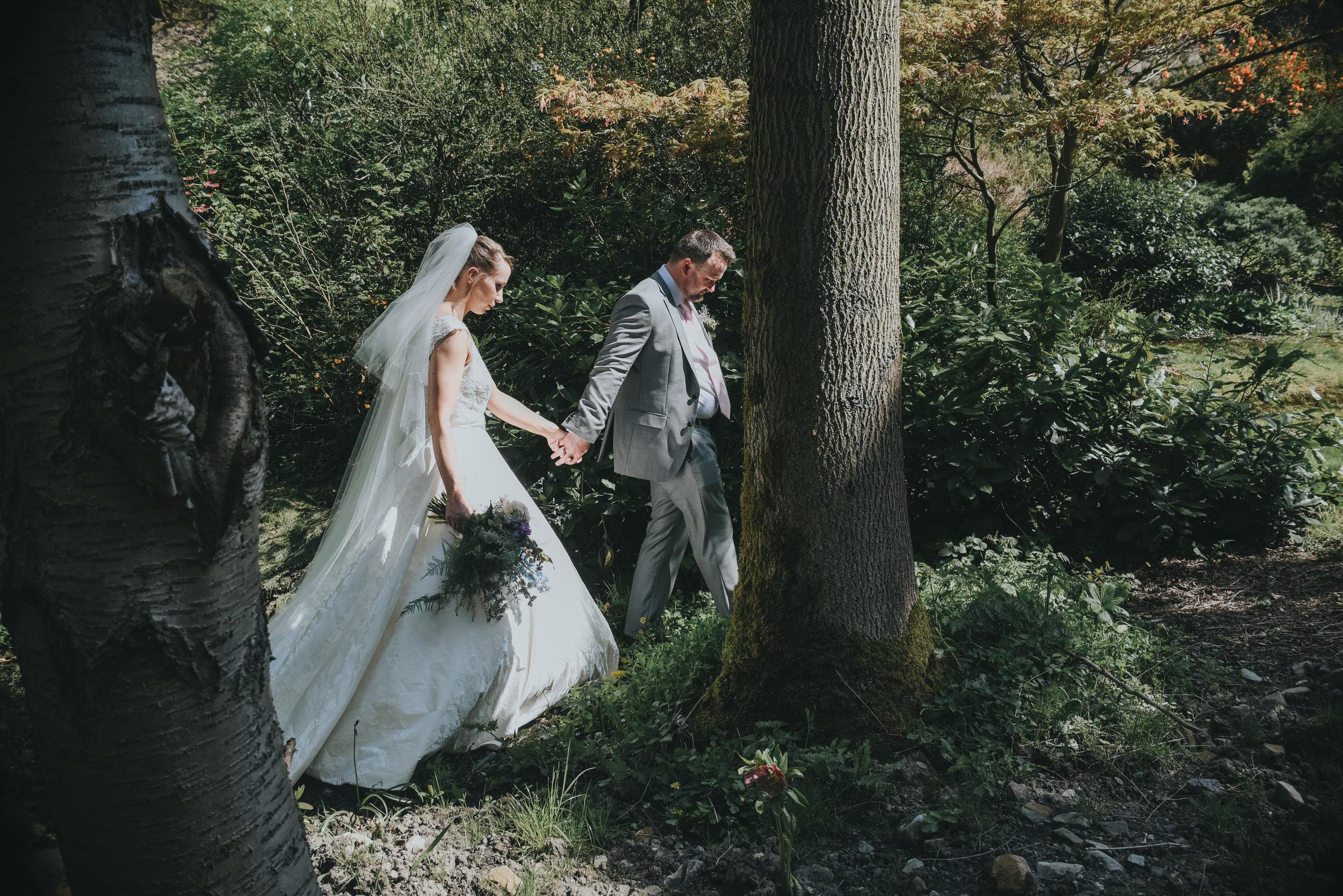 bride and groom walking between trees
