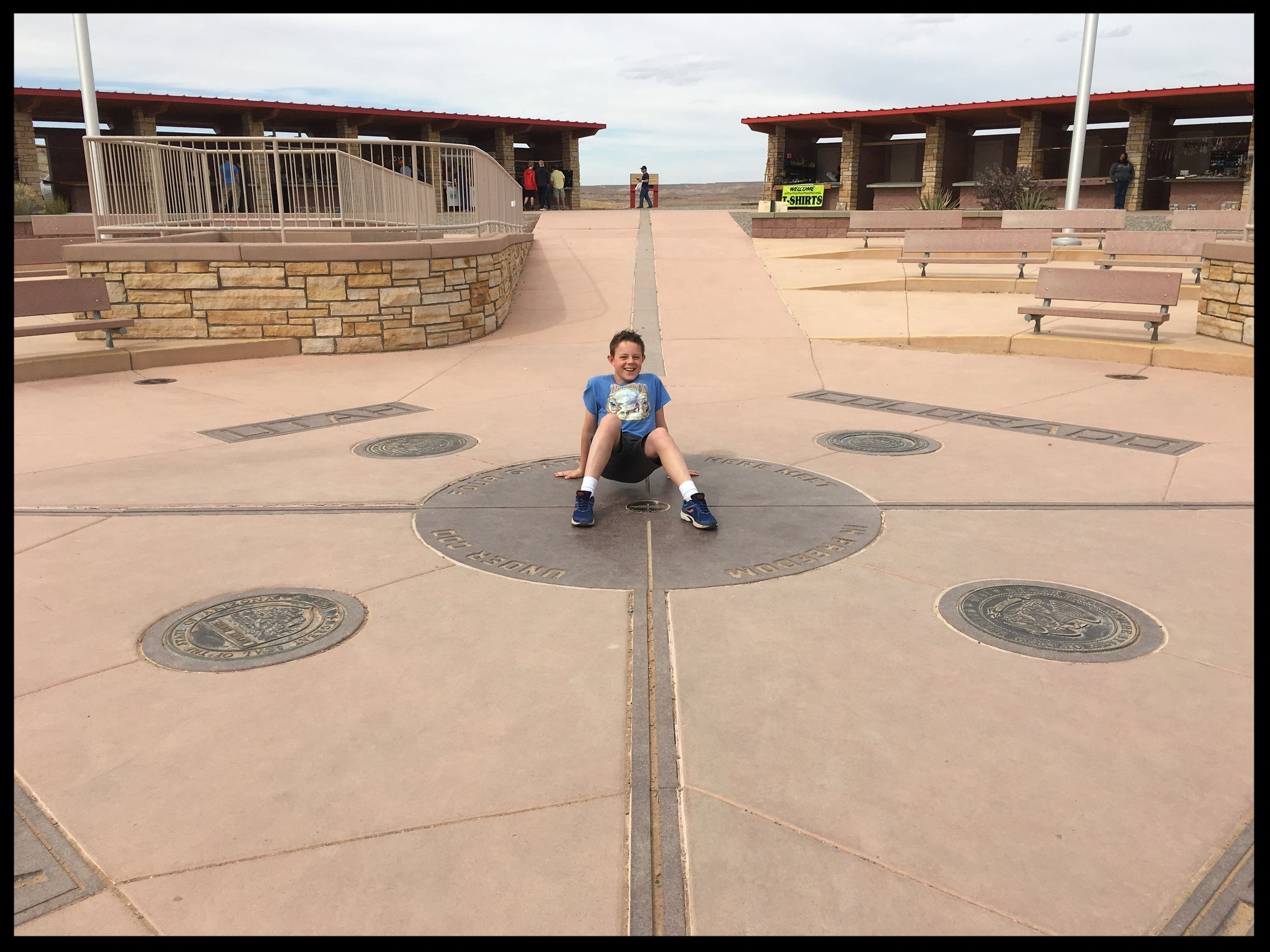 Brody posing at Four Corners Monument, our family's first trip to the site, where visitors can claim to be in four states at one time.  Photo by Michael Mundt.