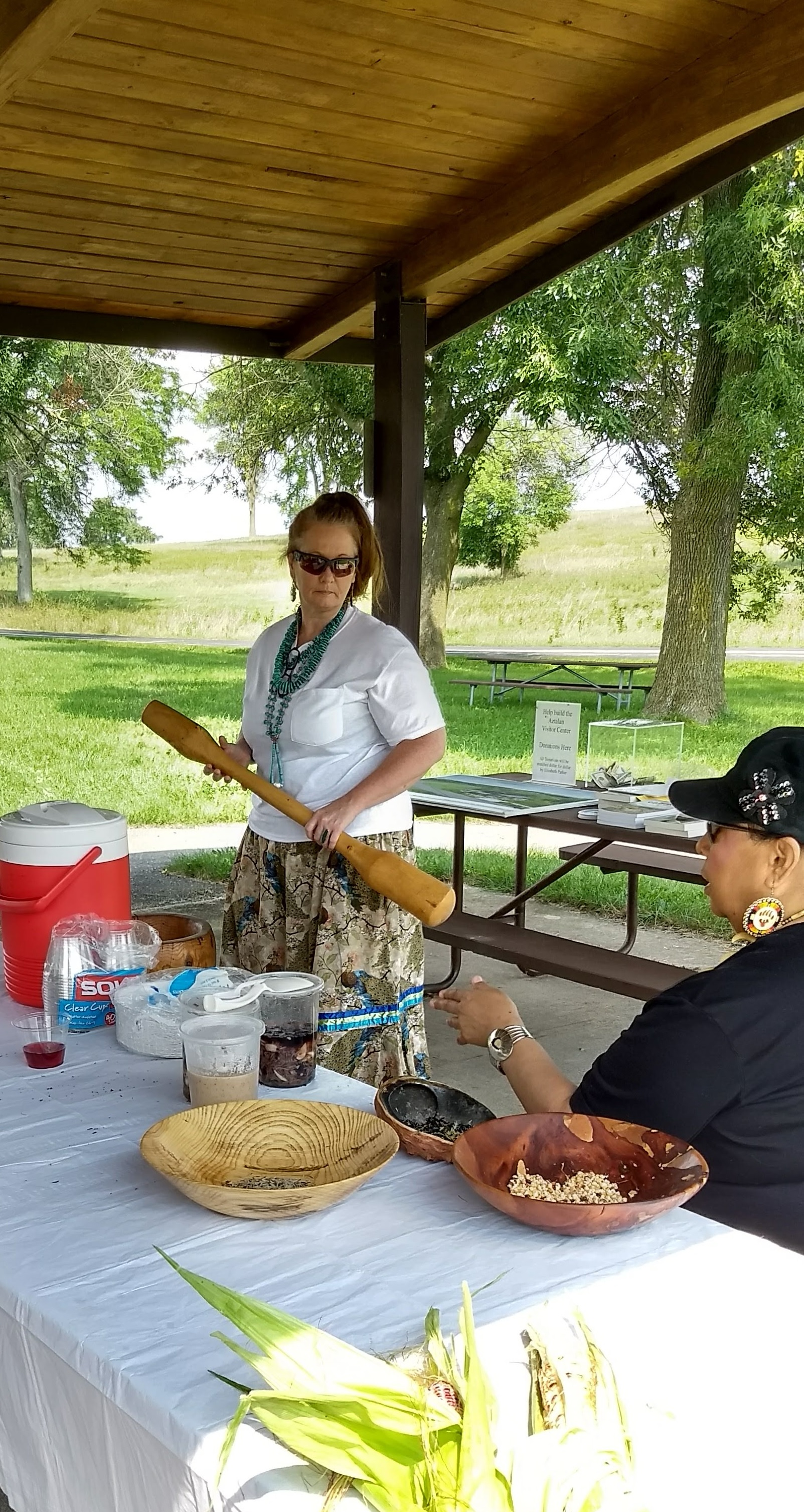 Rhonda Funmaker and Jodee Smith, with the corn pounder