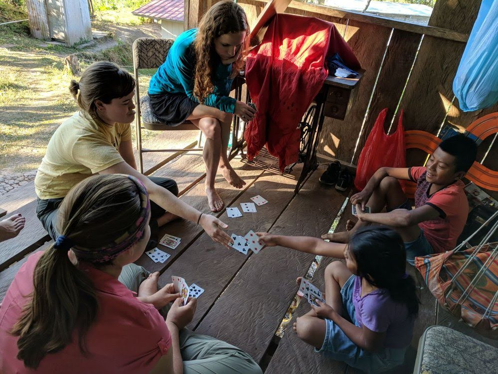 Bailey, Abby, and Katie playing cards with the kids.
