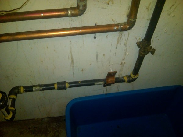 Looking at the gas line, we see copper clamp on black pipe. Again the support is falling from the wall and the teflon is used for tread joints instead of pro-dope. Gas pipe run is approxiamately 20' long and supported from the water heater and gas riser only. With no support in between!