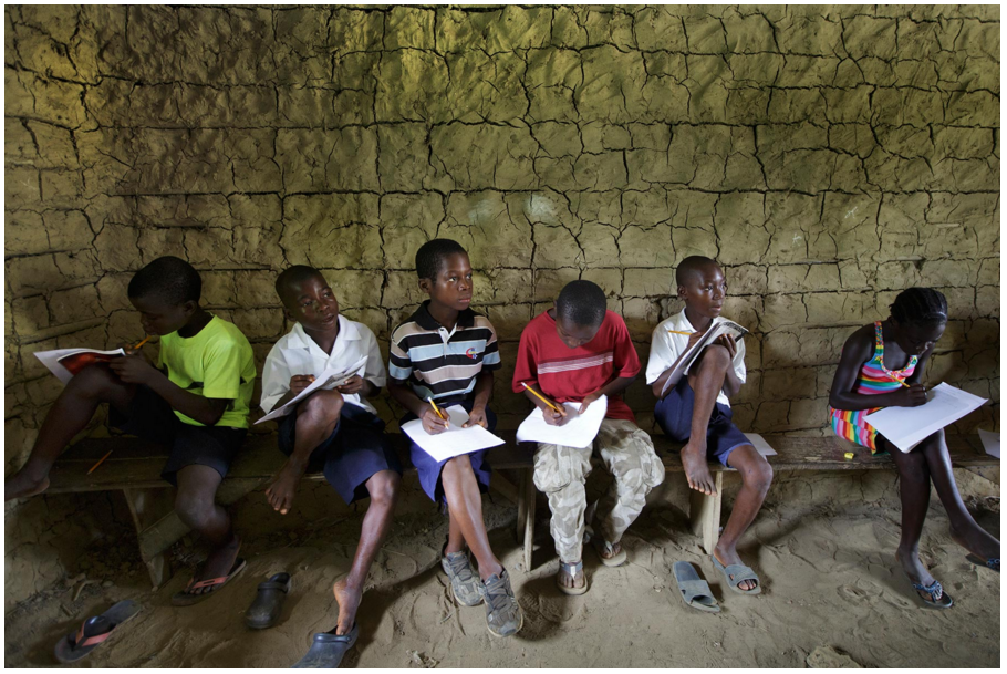 Palm oil companies promise to bring development to the villages they operate in, often in the form of education. Here, students study in a classroom in Grand Bassa, built by Equatorial Palm Oil. Photo by Kuni Takahashi.