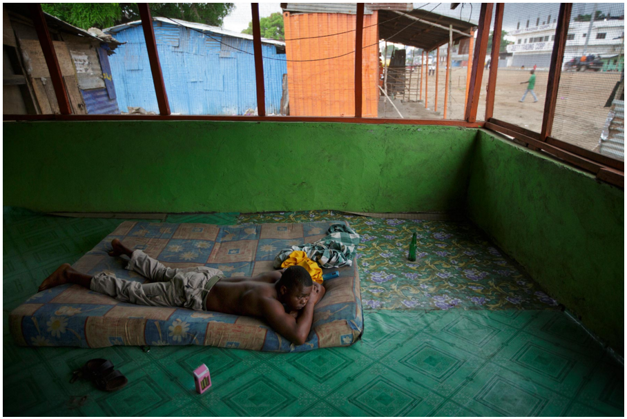 Momo Dukoe lays on a mattress in a restaurant where he sleeps during the night.