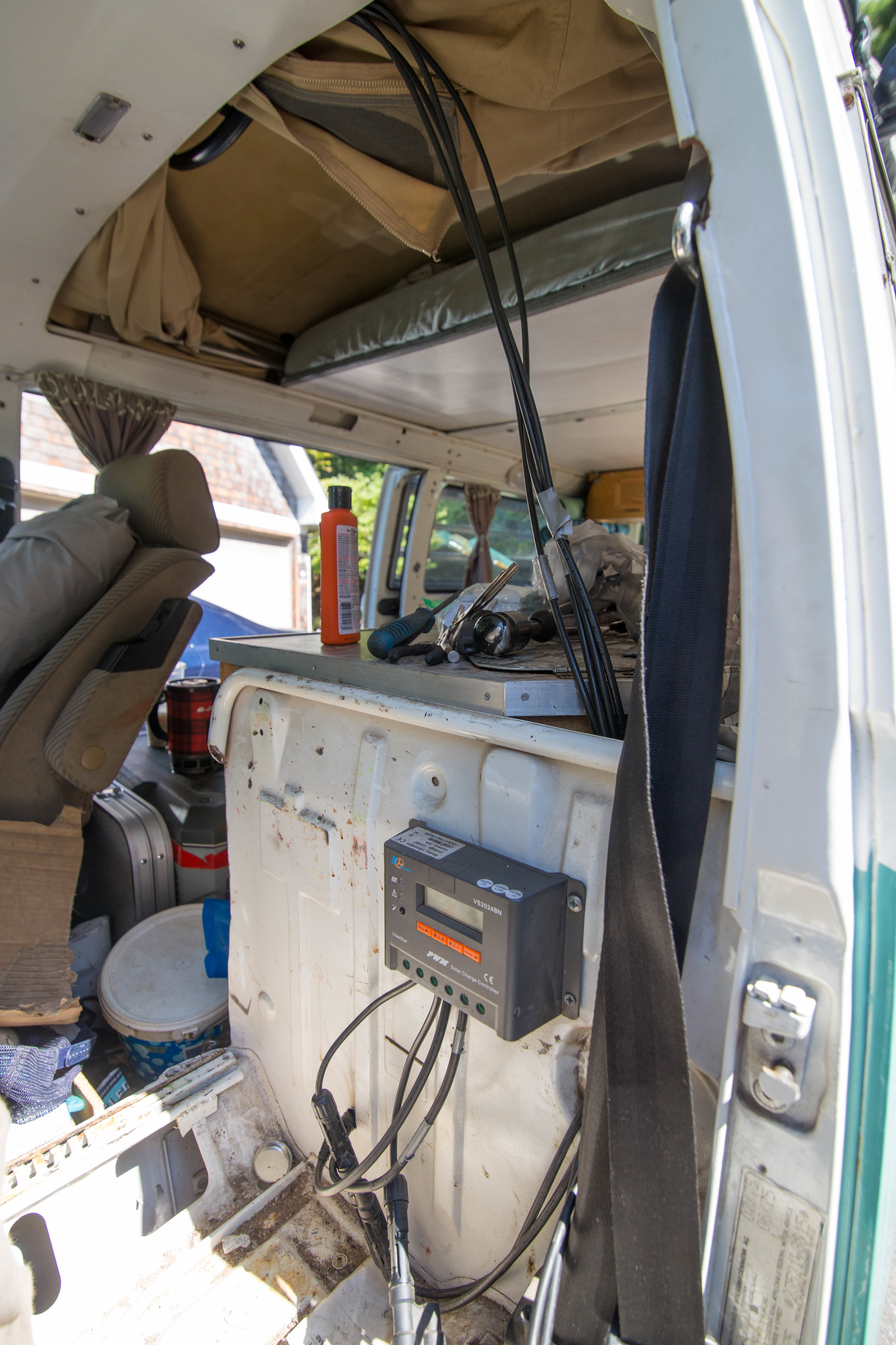 The wires are pulled from behind the headliner, secured near the driver's seat belt, then routed behind the bulkhead. I drilled a two holes in the bulkhead, one for the panel wires to the controller and one for the tray wires, from the controller to the battery in the engine bay.