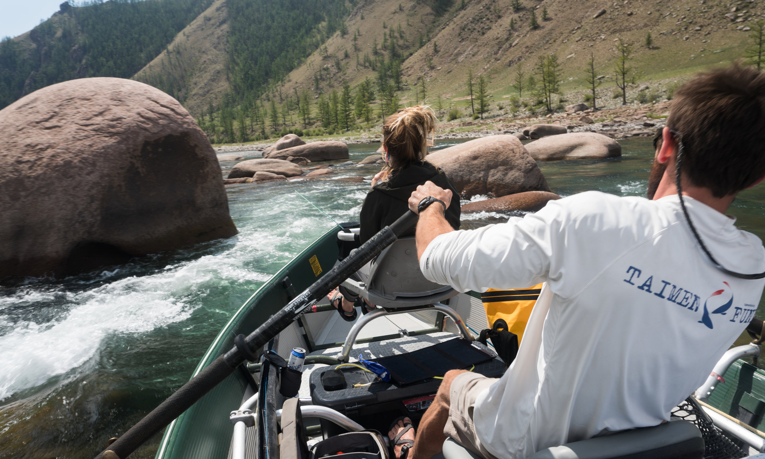 Fly fishing guide Mark Portman rowing a drift boat in Mongolia