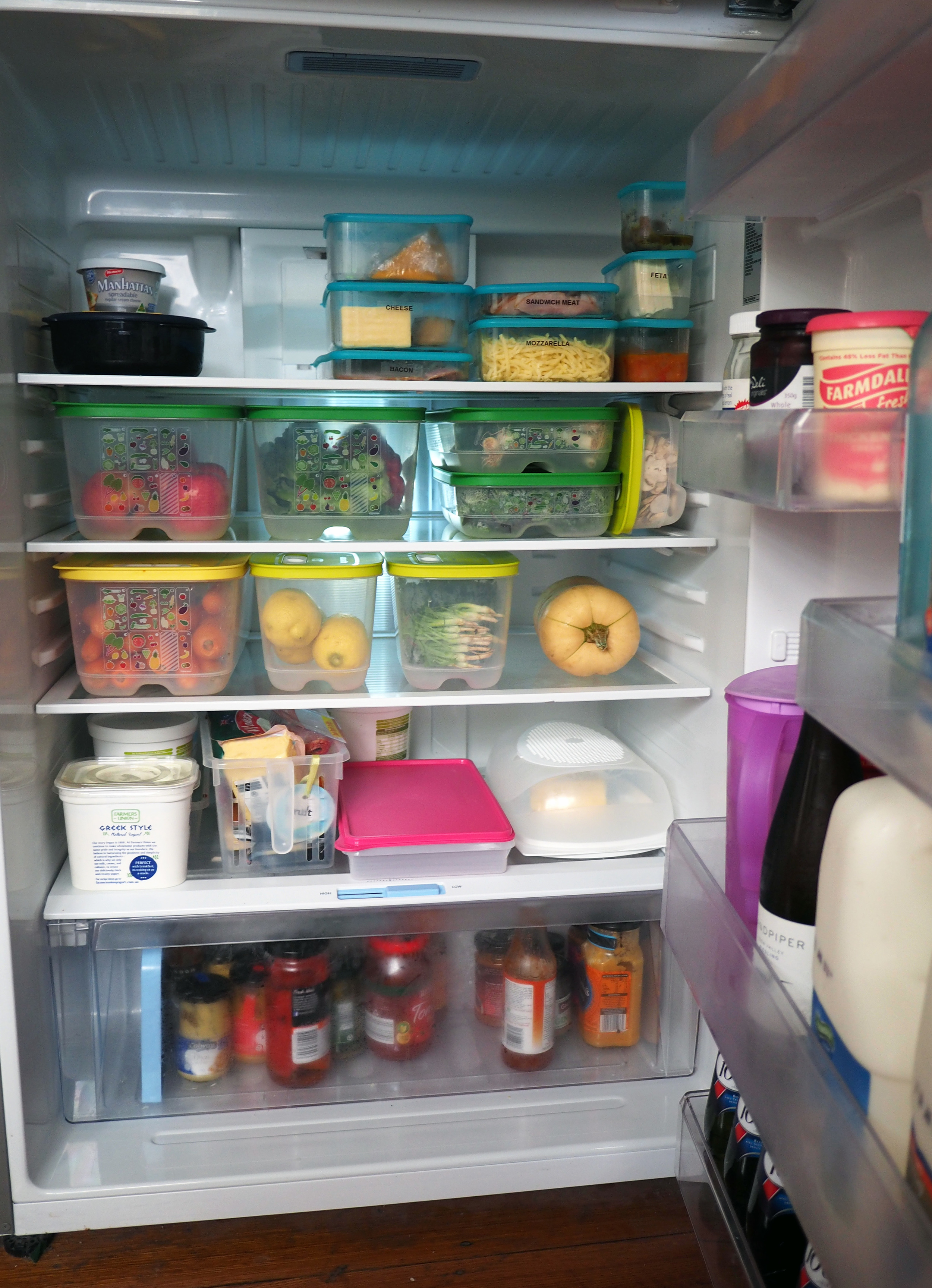 An organised fridge, using air-tight containers to seal and corral dairy items, and fruit and vegetable containers to ensure products last longer and everything is easy to find.