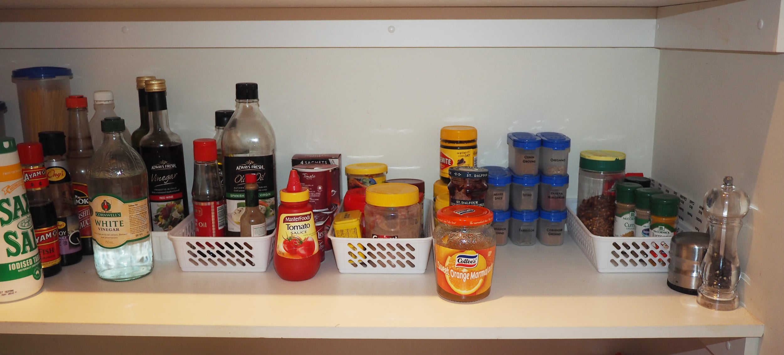 Organise condiments and spices by grouping like with like and using storage containers where possible