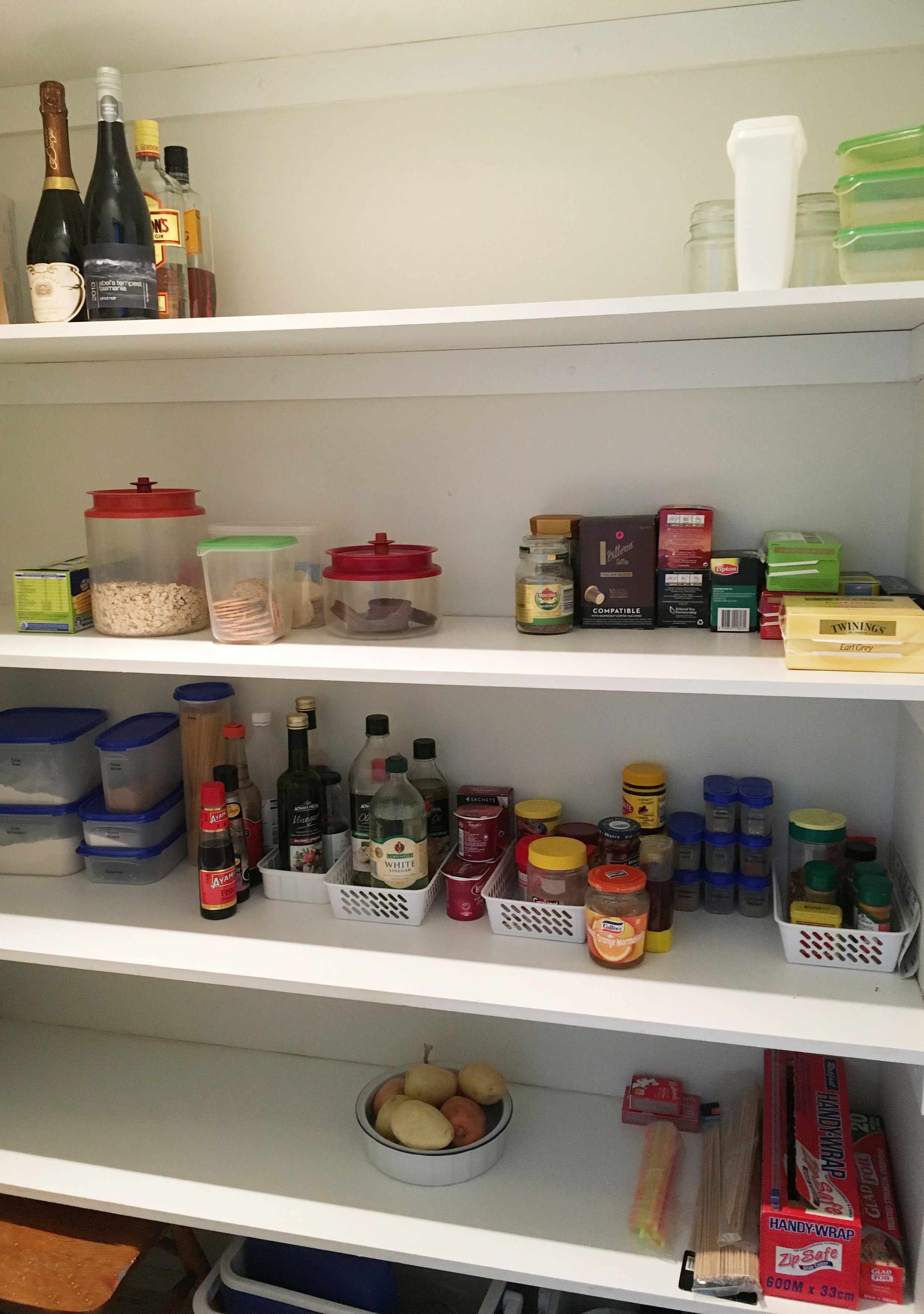 An organised pantry at a holiday house with food organised by categories, and grouped according to ease of accessibility