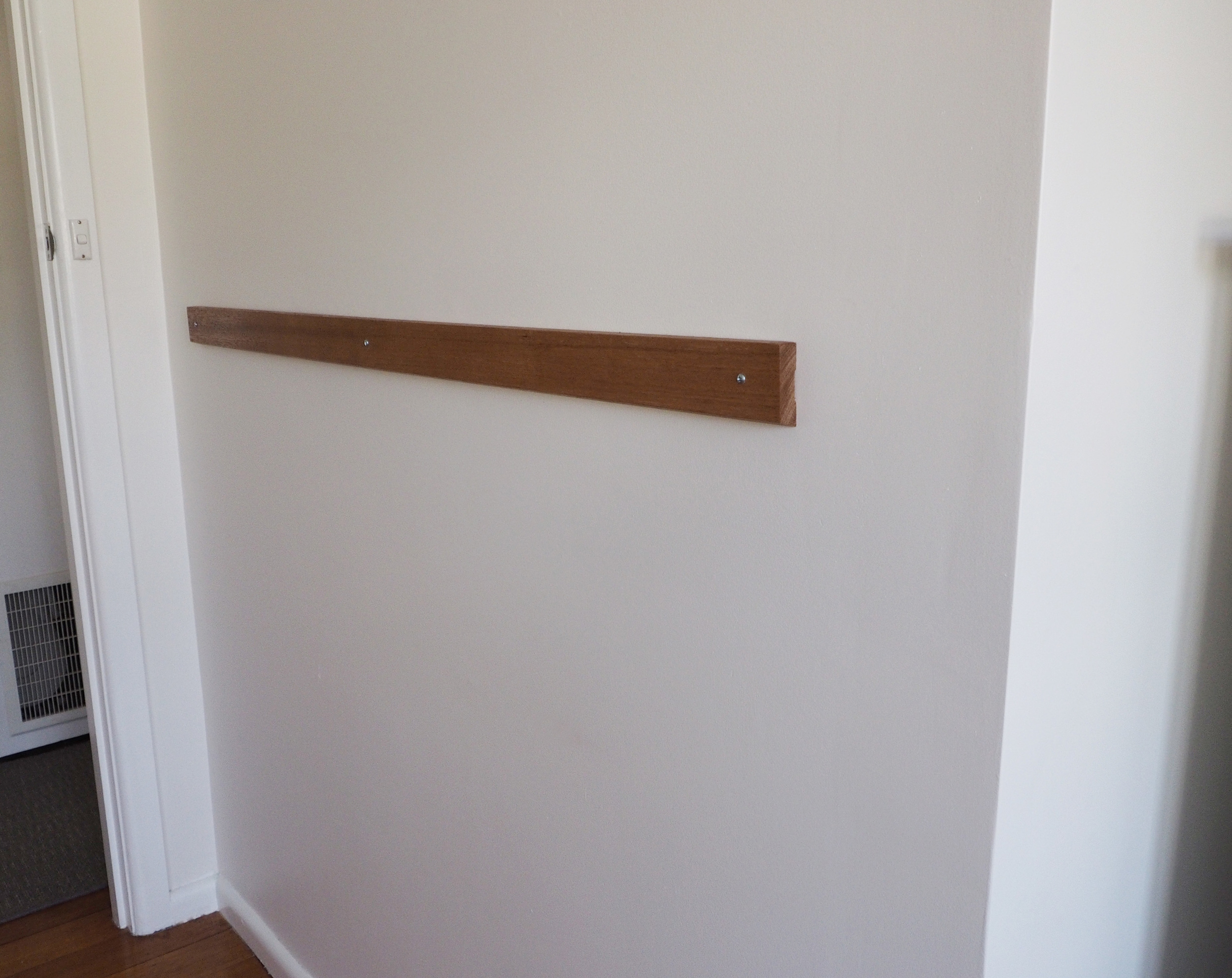 A piece of wood attached to a blank wall can be the perfect spot for an easy art display