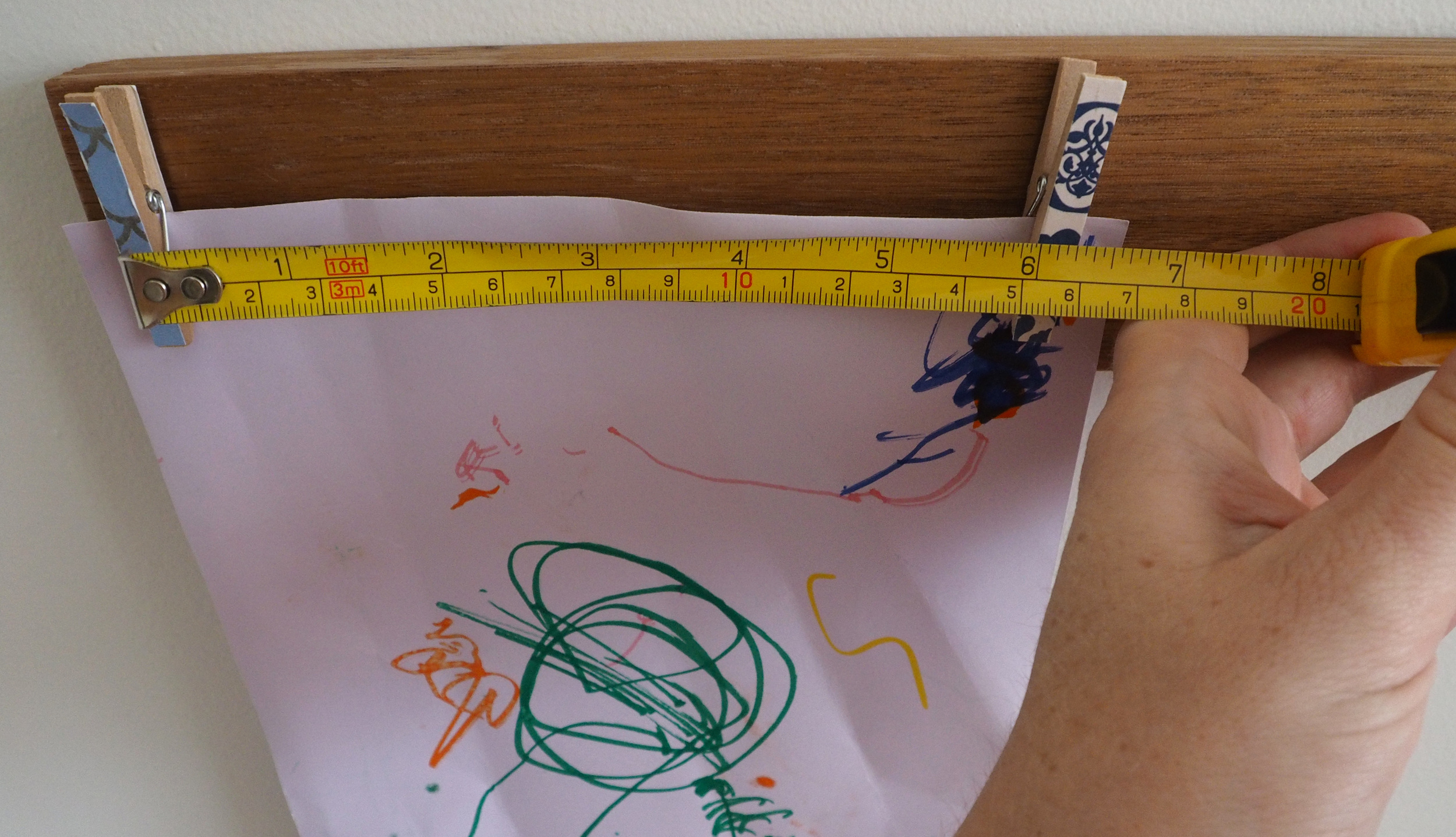 Measuring distance between the pegs to hold artwork efficiently