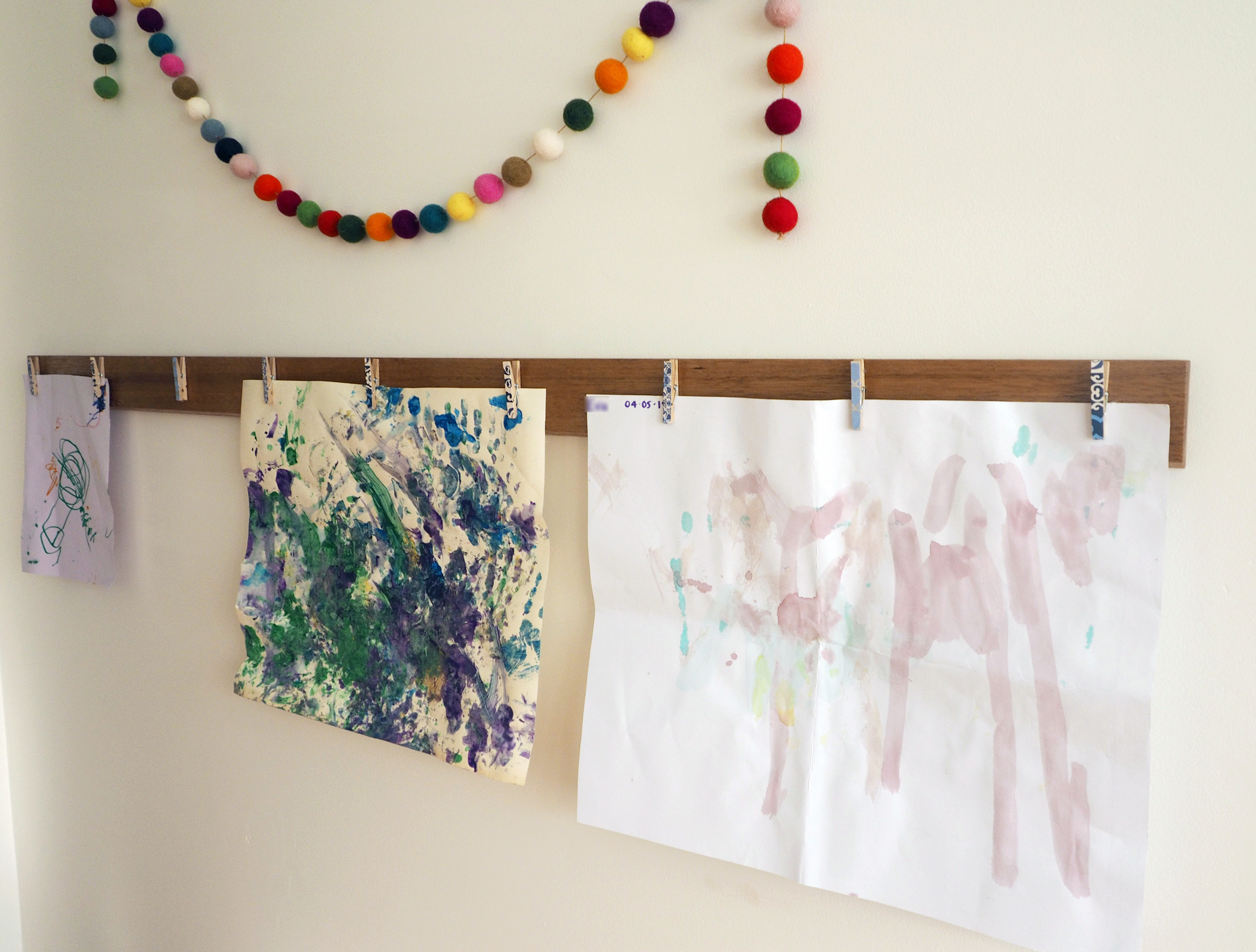 A felt ball garland and child's artwork make a pretty decorative display in a bedroom