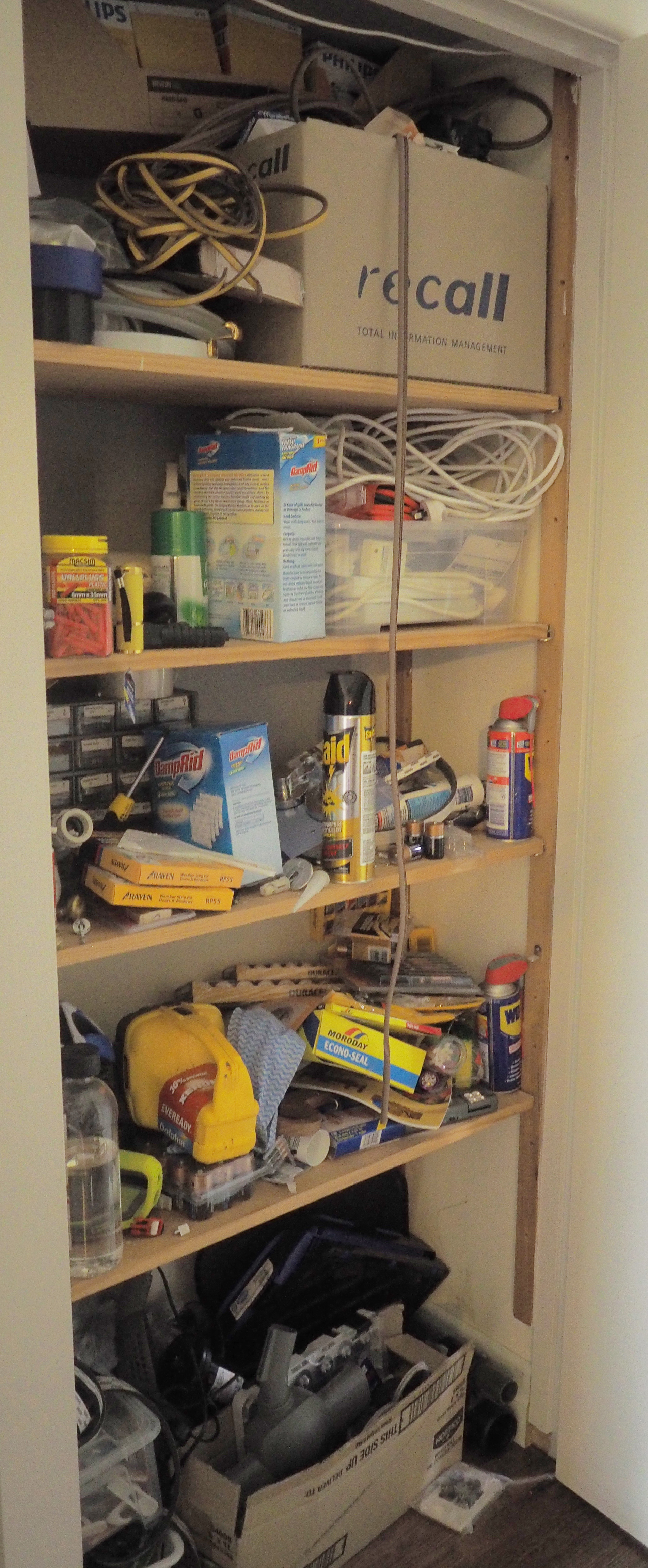 Cupboard disorganised before makeover