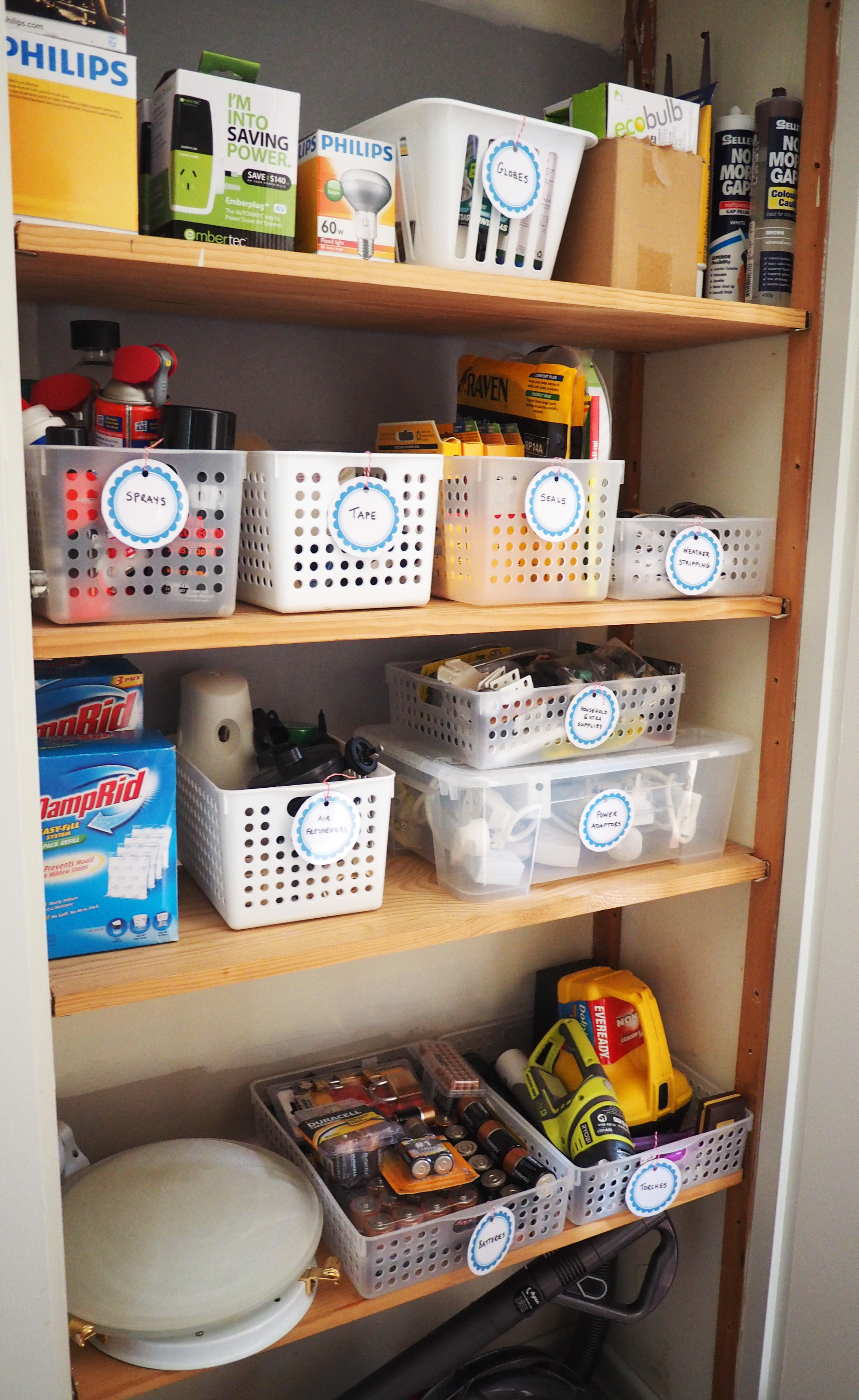 Storage cupboard organised using open baskets with labels