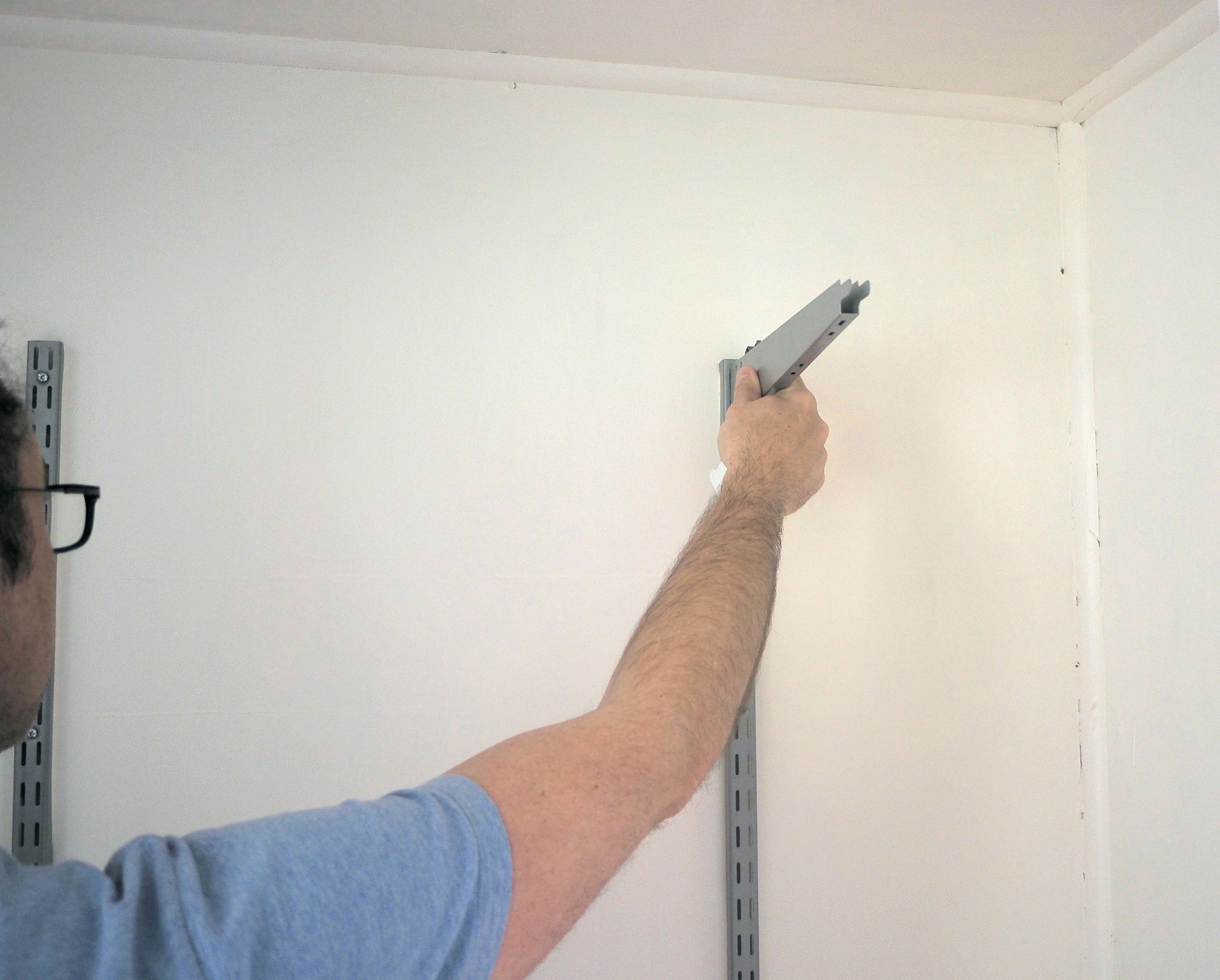 Attaching brackets to the inside of a wardrobe  for our son's bedroom makeover - The Organised You