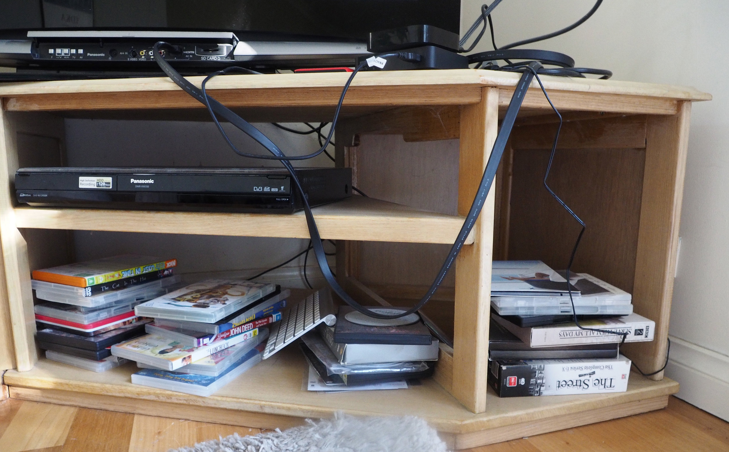 Does this cord clutter on the  TV unit look familiar to you? Learn how to fix it with these simple strategies for organising cords, click through to read!  {The Organised You}